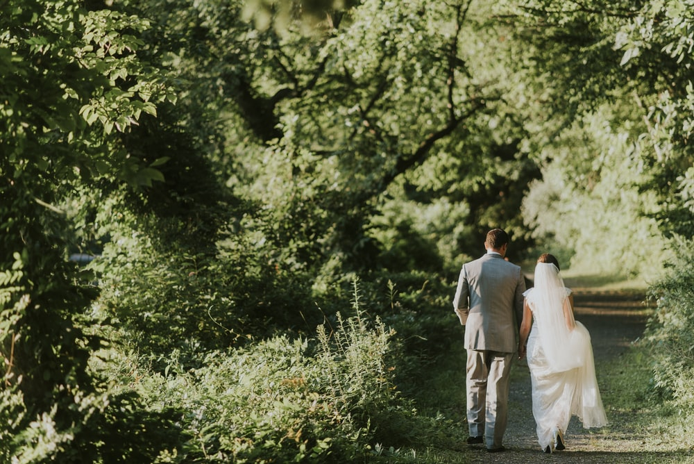 groom and bride walking on forest pathway photograph