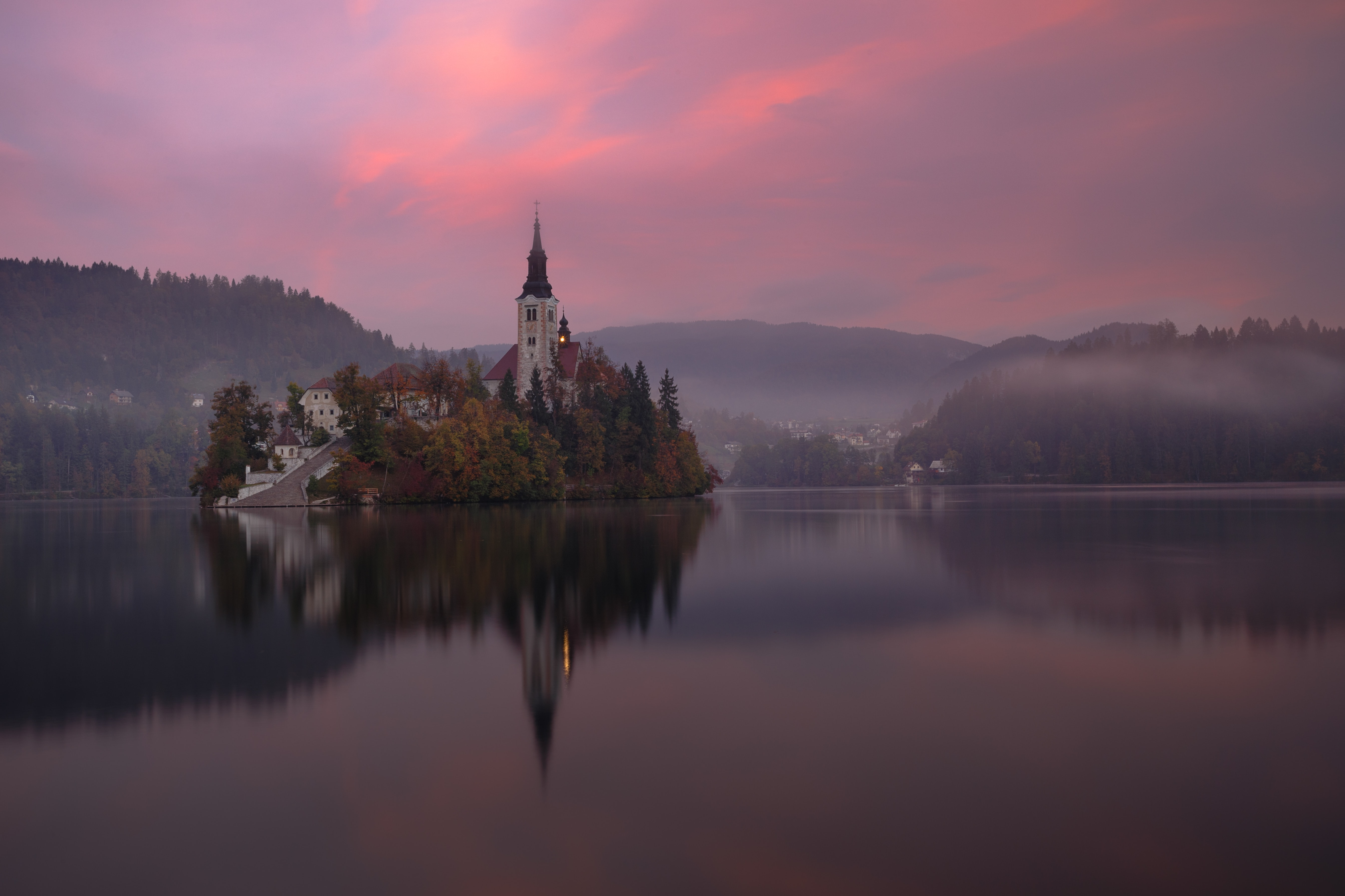 A village church and its foggy sunset scenery are reflected upon the waters of Lake Bled in Slovenia