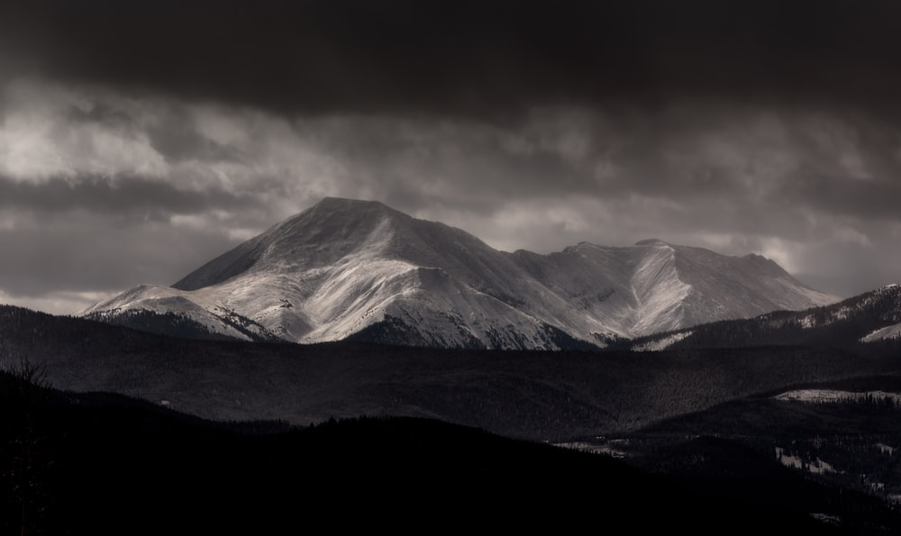 grayscale photography of mountain under cloudy sky