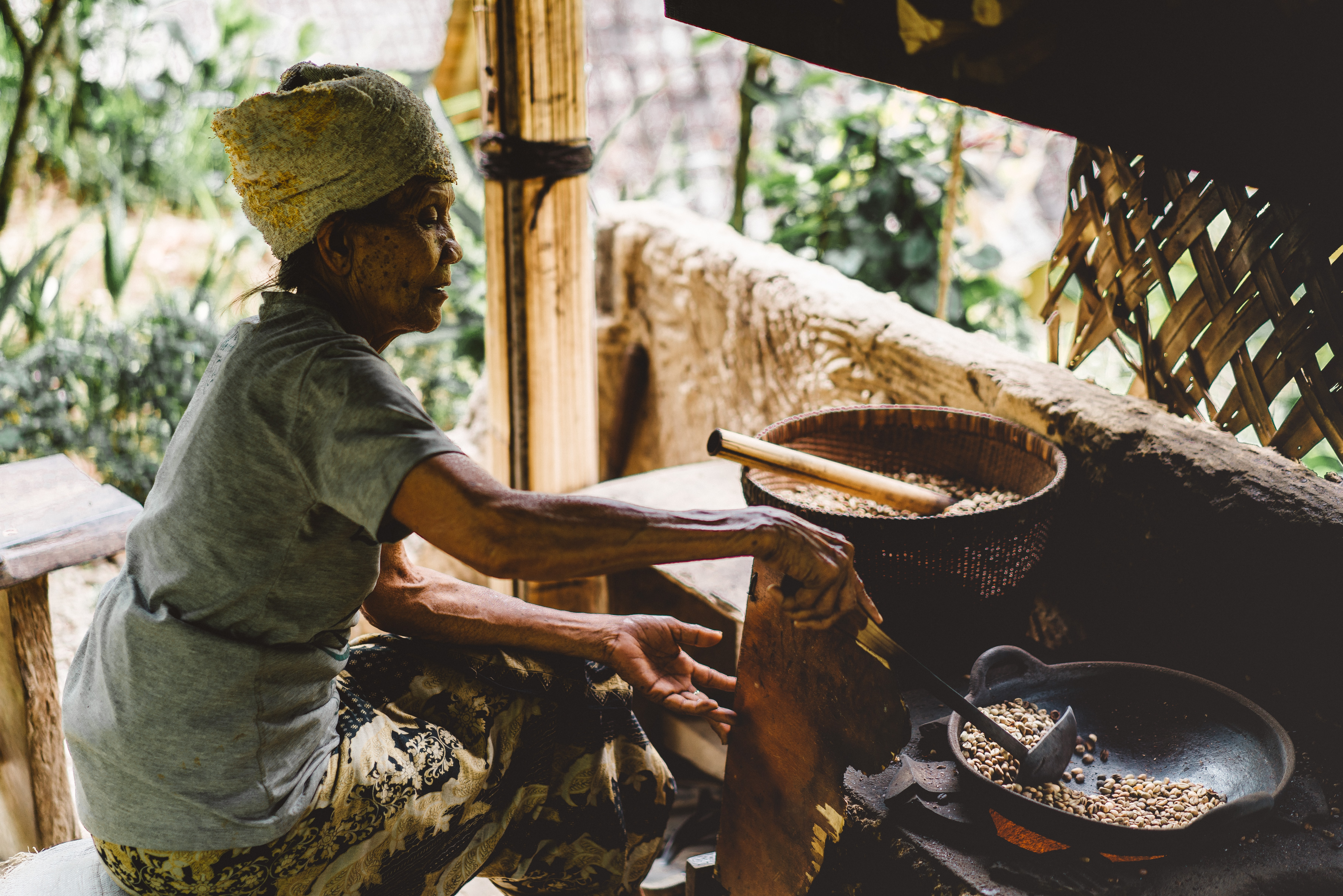 An old woman is sitting by the stove cooking beans with a spatula and a wok.