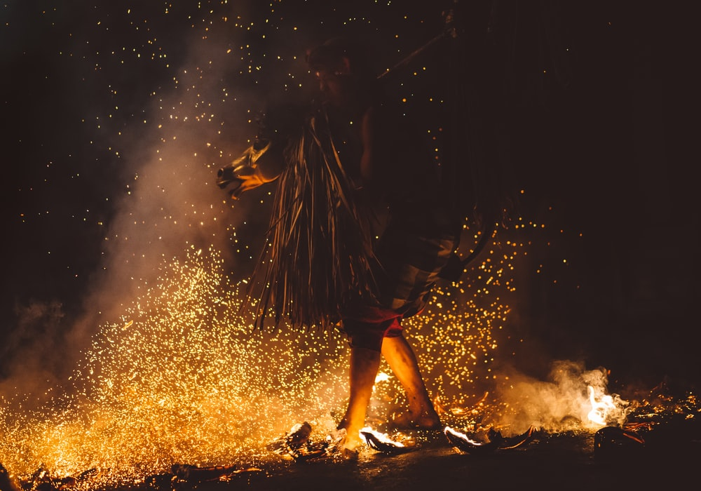 A man walking on fire with his feets burning and sparks every where in Ubud