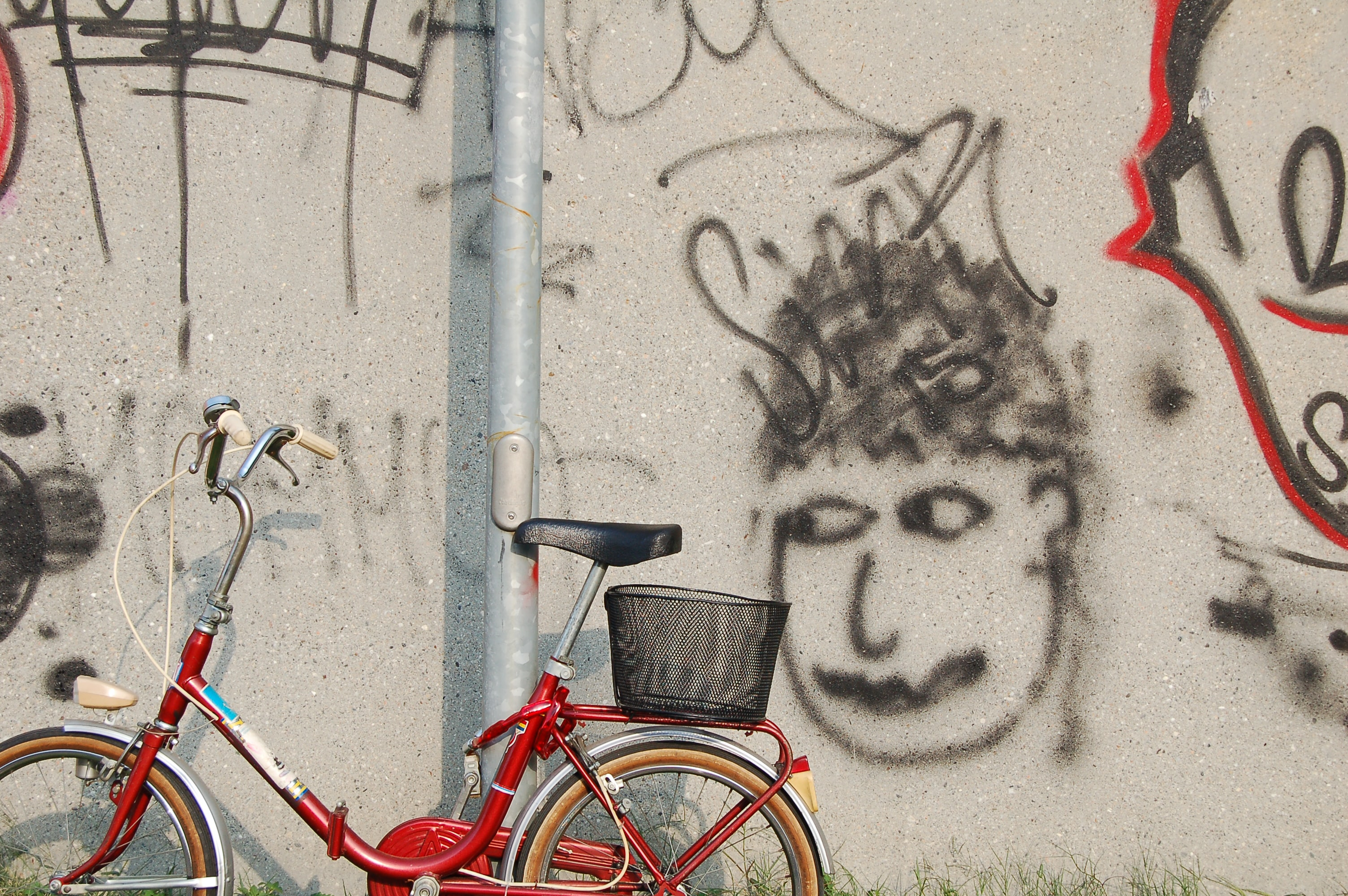Red bicycle with basket in front of wall with graffiti