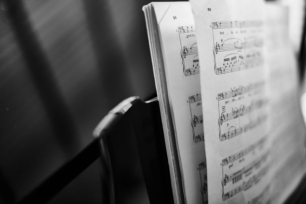 A black and white shot of an open music score on a stand