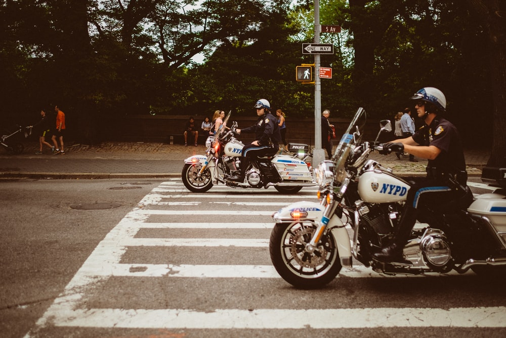 two policemen riding motorcycles on road
