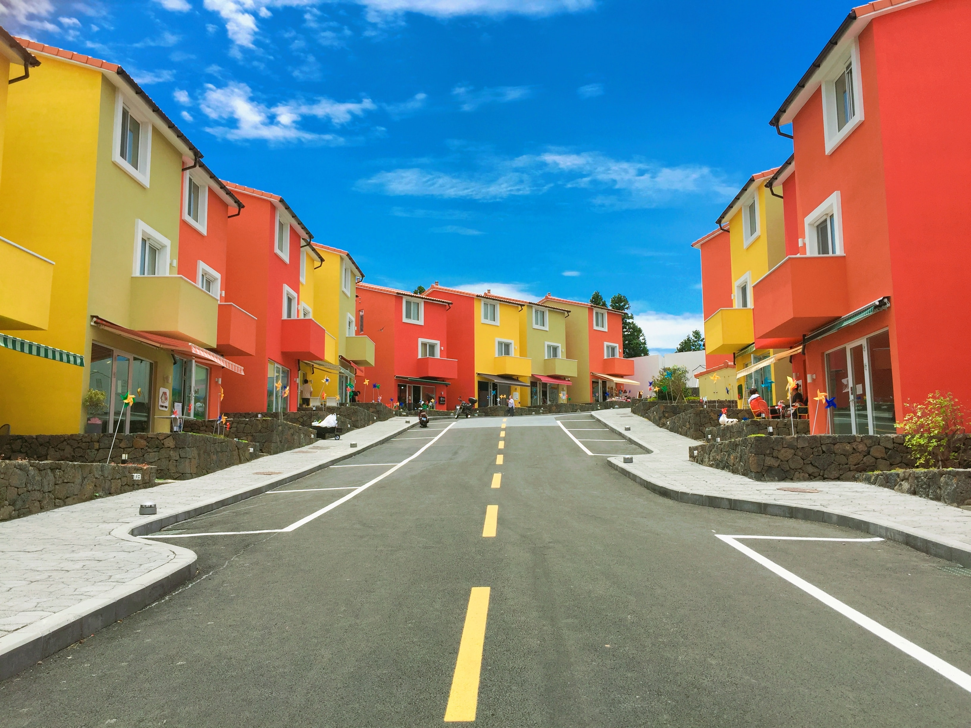 Road with bright red and yellow colored houses with windows, and brilliant blue sky