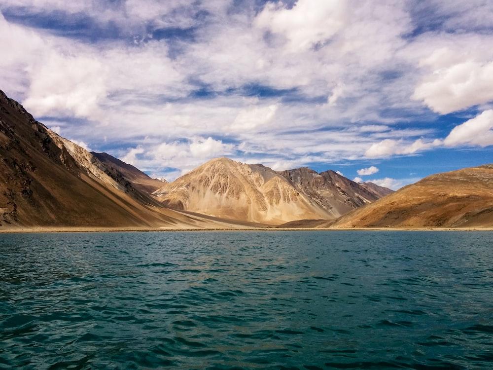 calm sea near mountains under white cloud blue skies