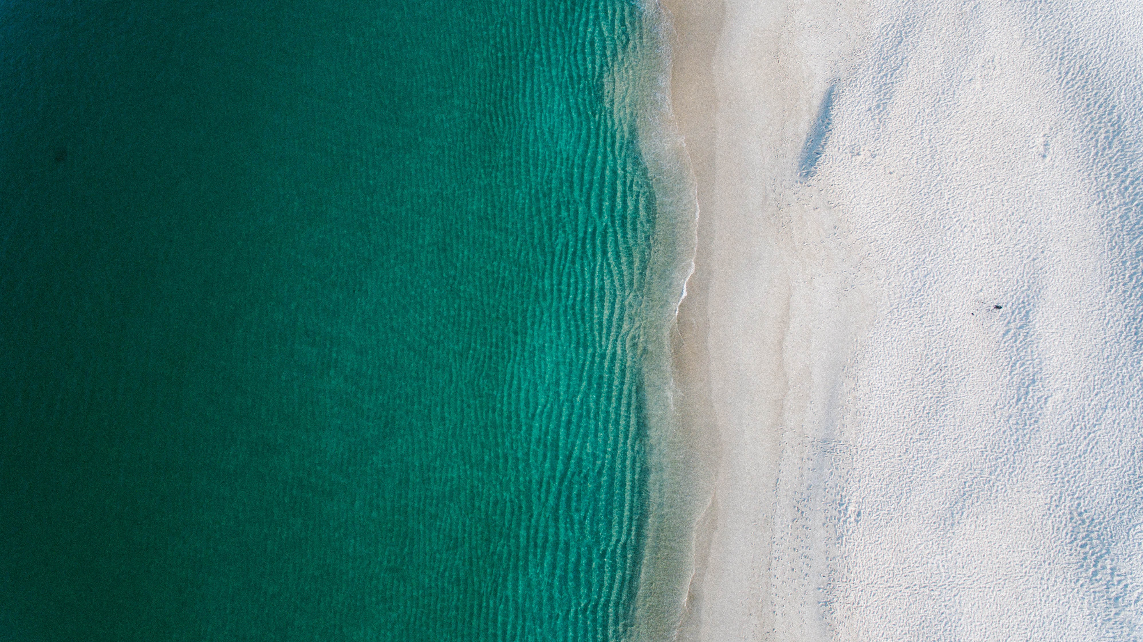 Drone view of a clear ocean washing up on sand shore in Nelson Bay