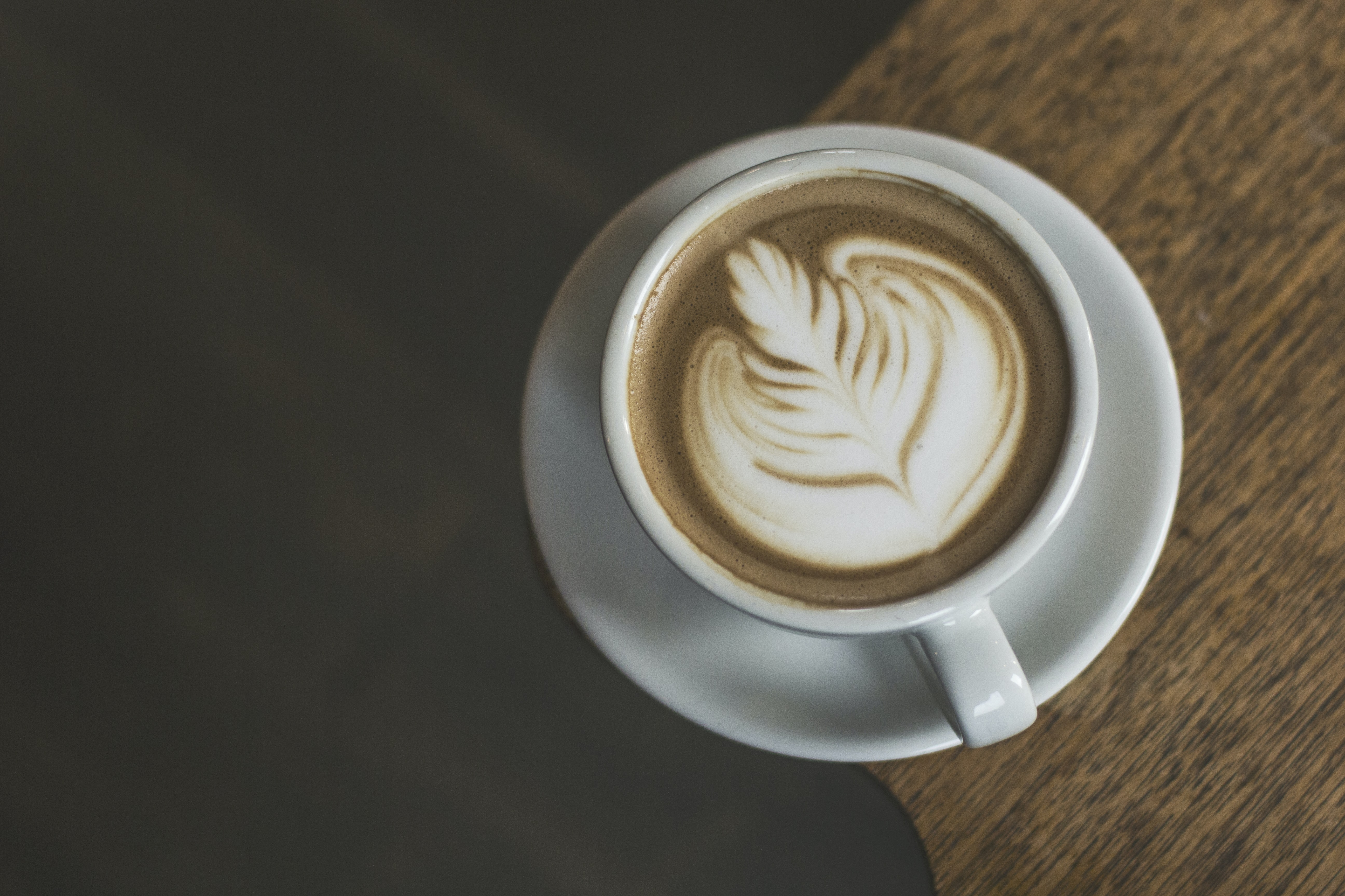 Latte with foam leaf-like art in a white coffee cup on a wooden table