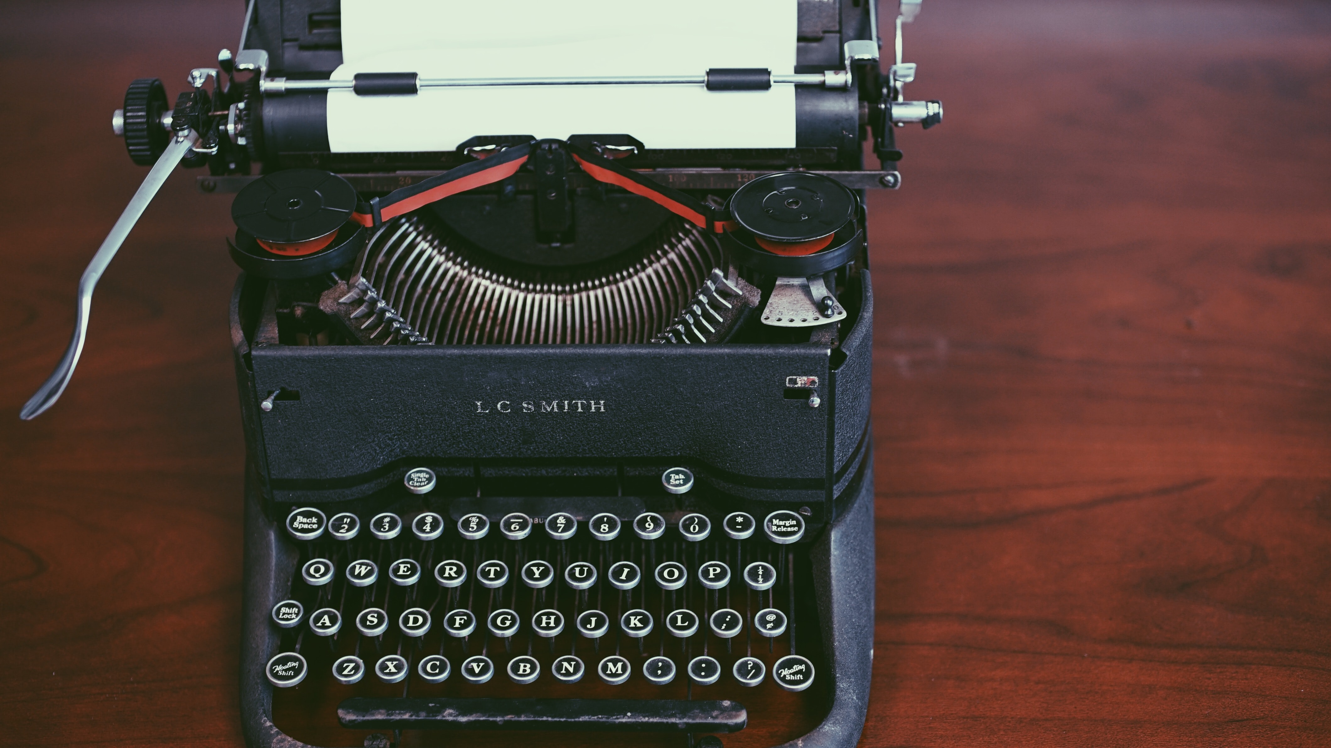 An old black LC Smith typewriter on a wooden surface