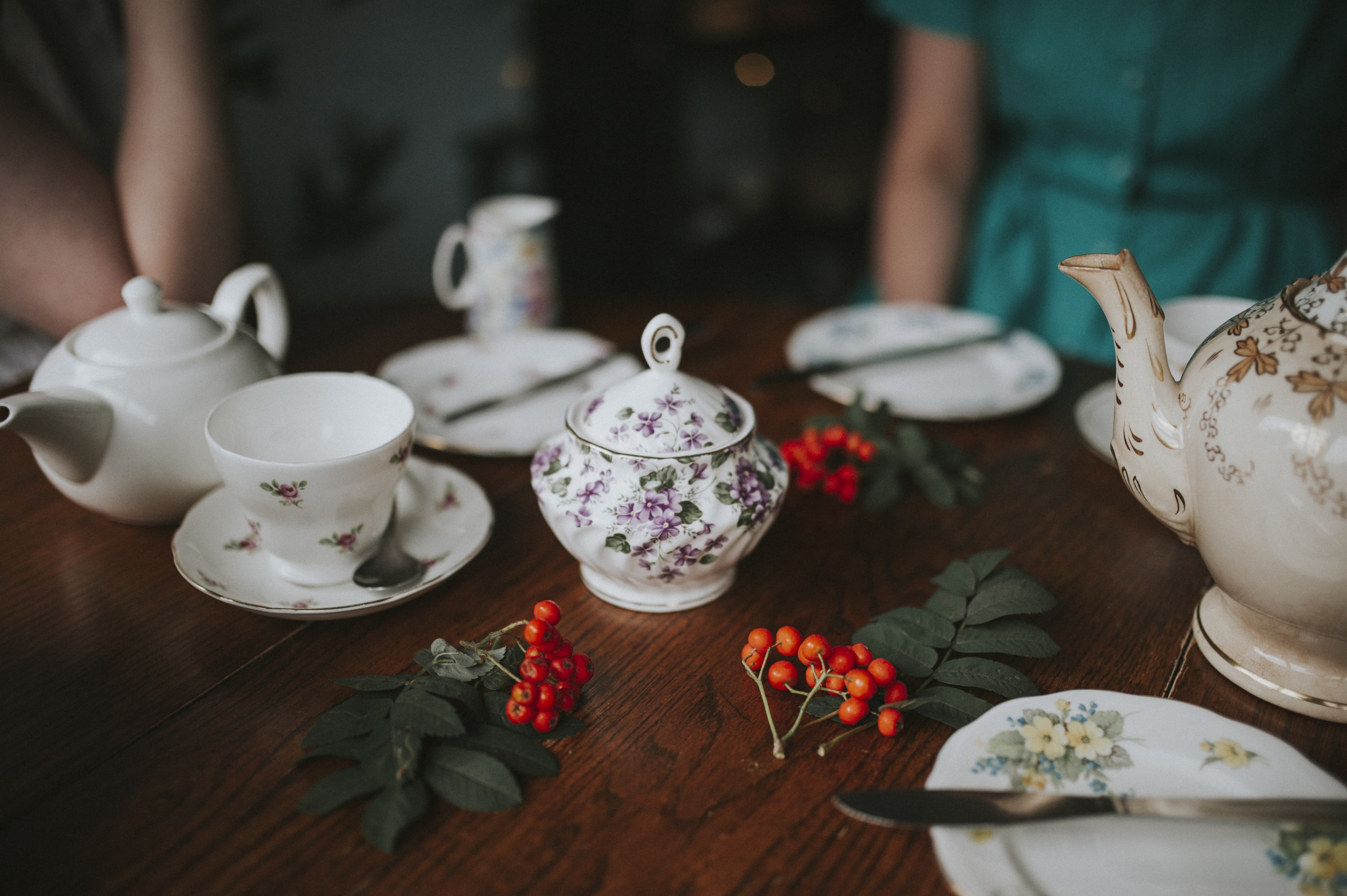 photo of white floral tea set on brown wooden table