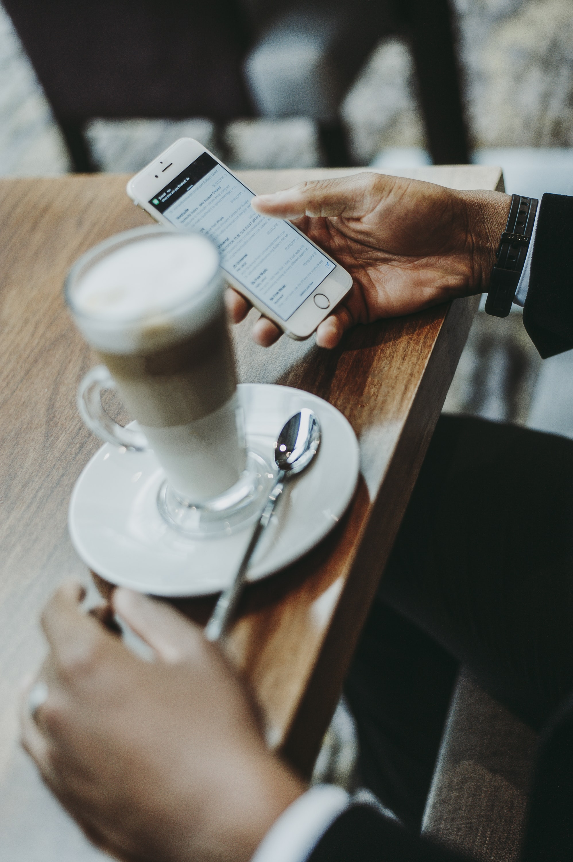 A man in a suit using an iPhone while sitting over a tall coffee