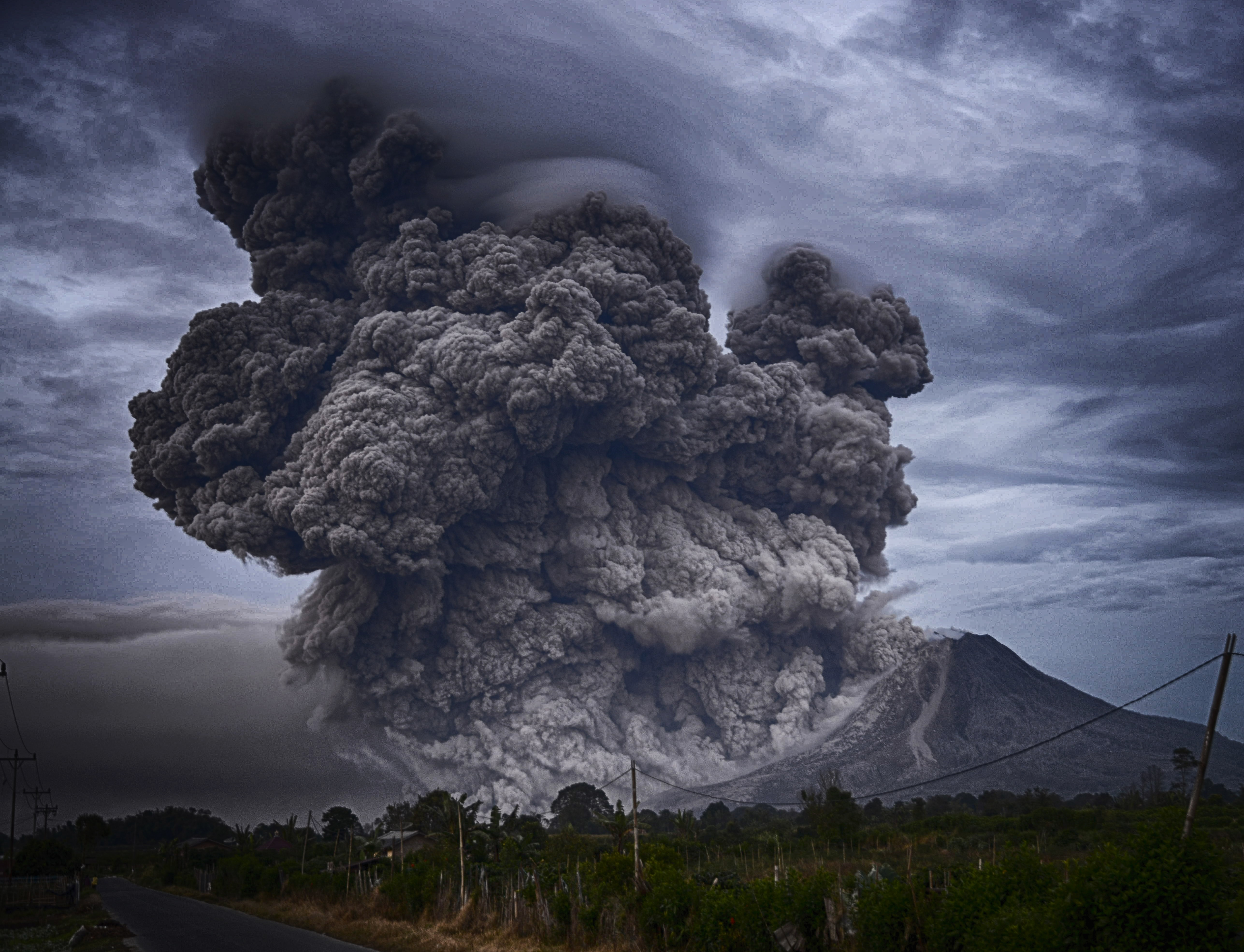 A tall cloud of volcanic ash rising up from a slope of Mount Sinabung