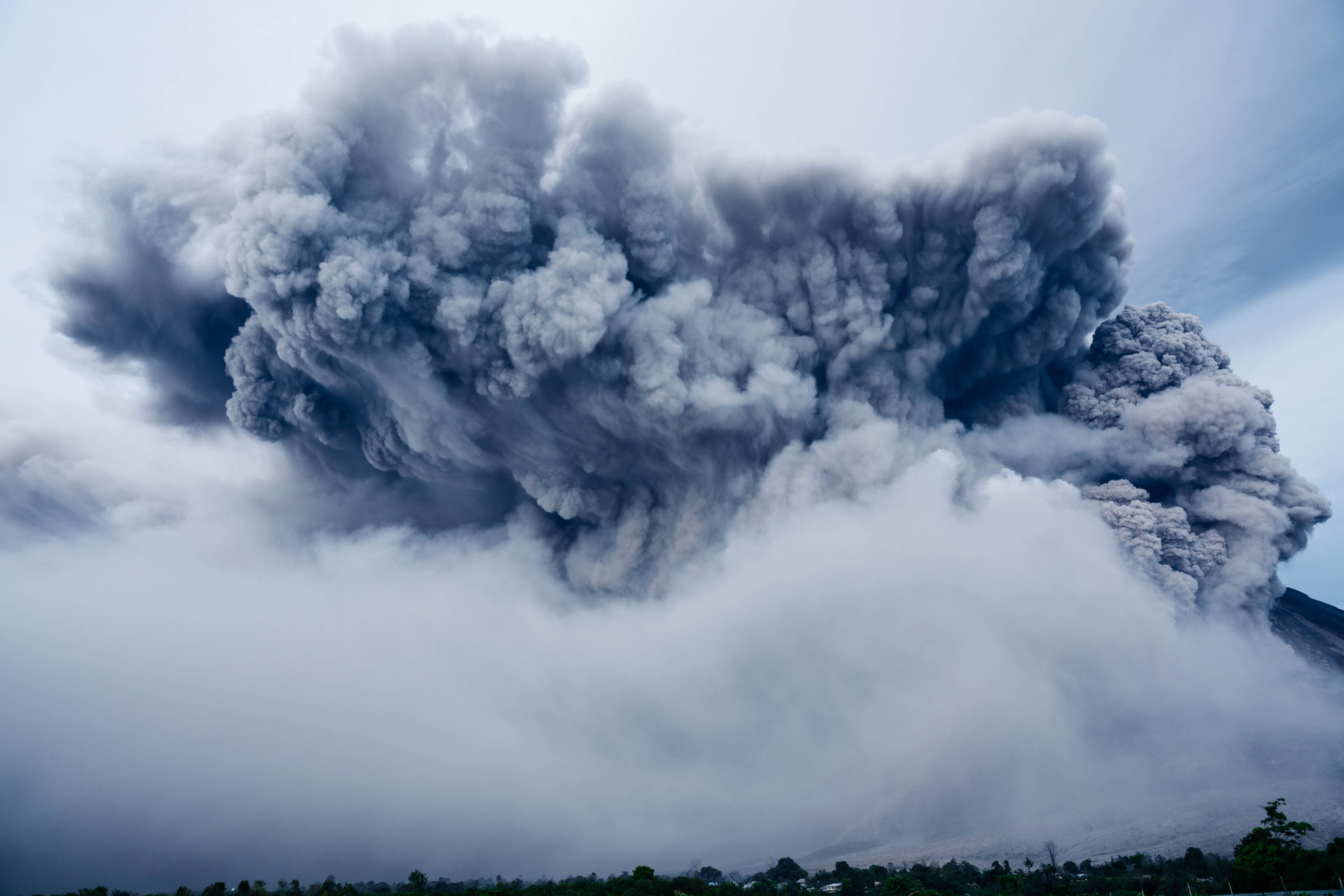 An enormous column of smoke over an erupting volcano