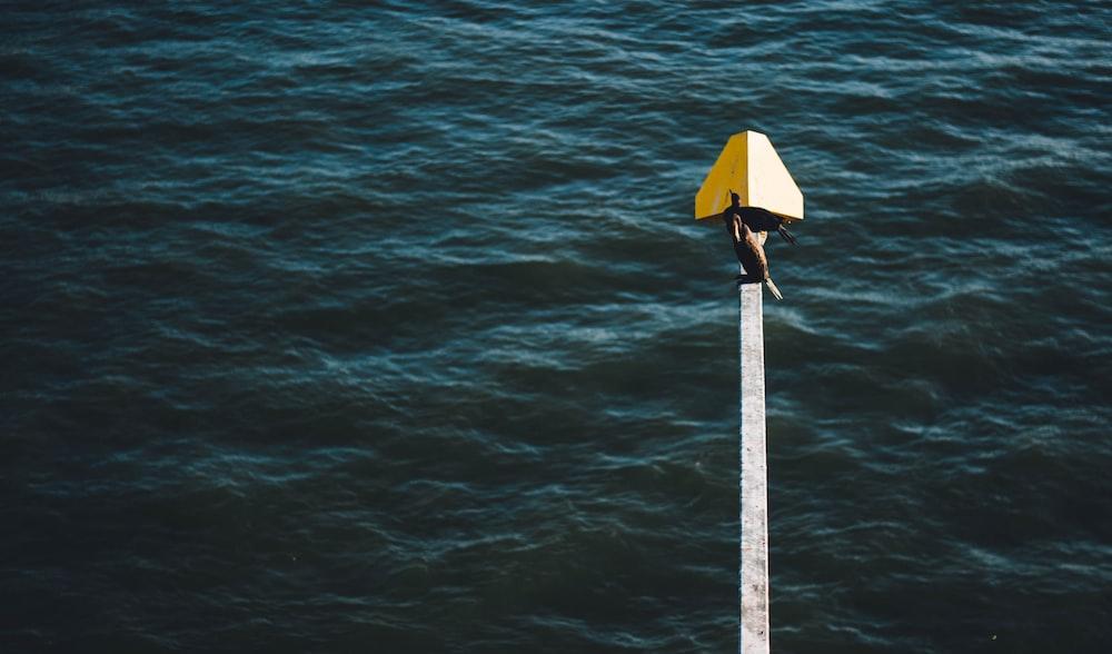 yellow umbrella on body of water