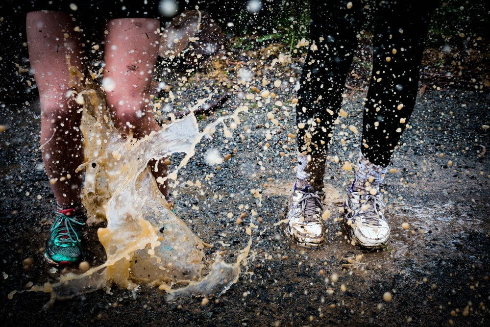 water splashing on two running people