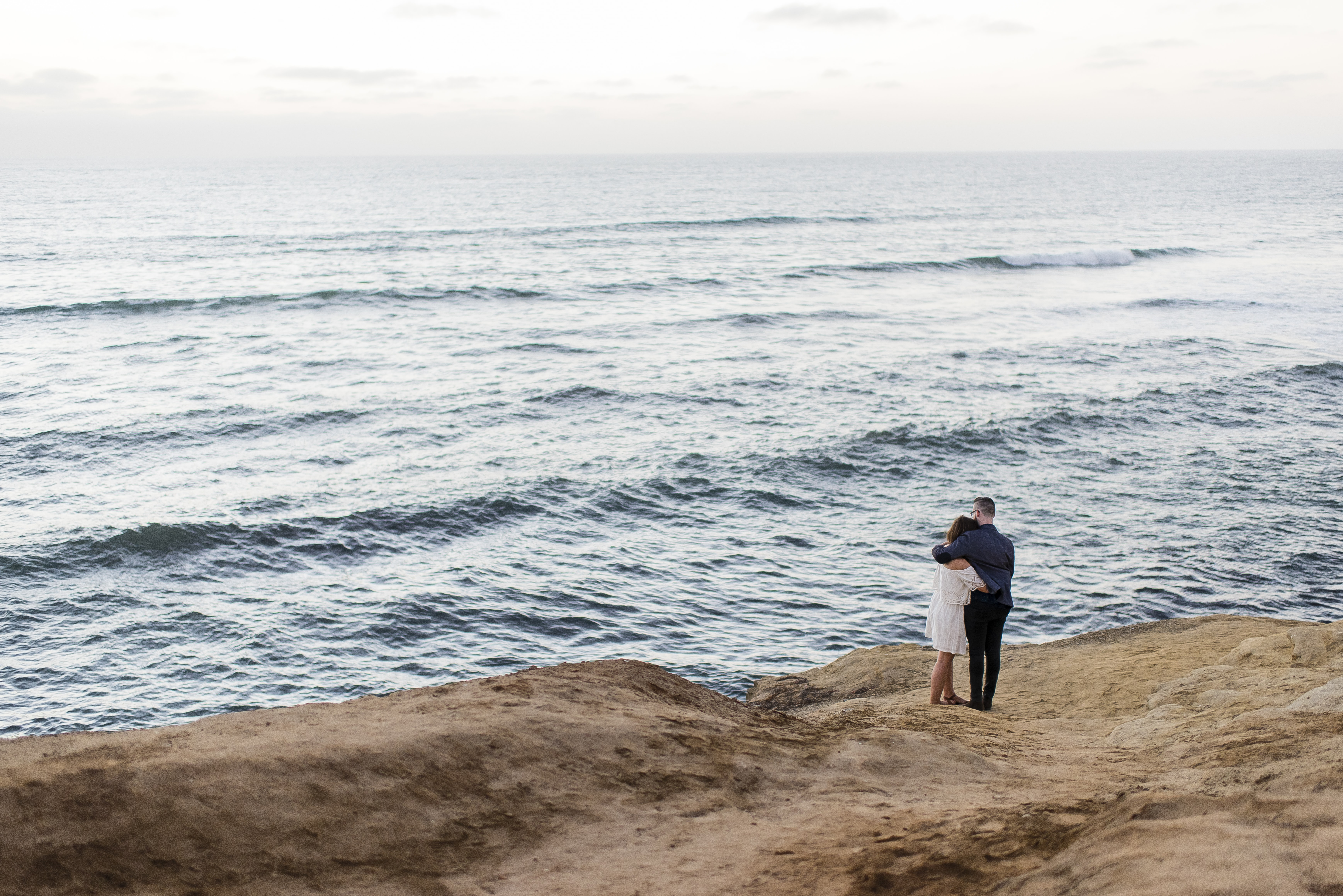 A couple stands on a rocky surface by the ocean, their arms around each other