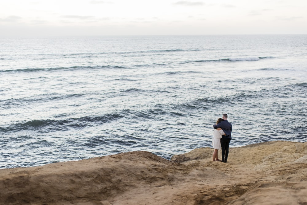 man and woman facing body of water