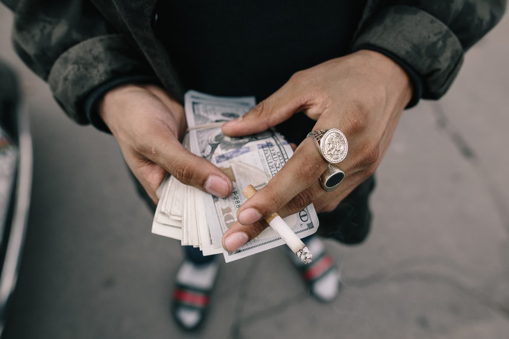 person holding dollar banknotes while pinning cigarette stick