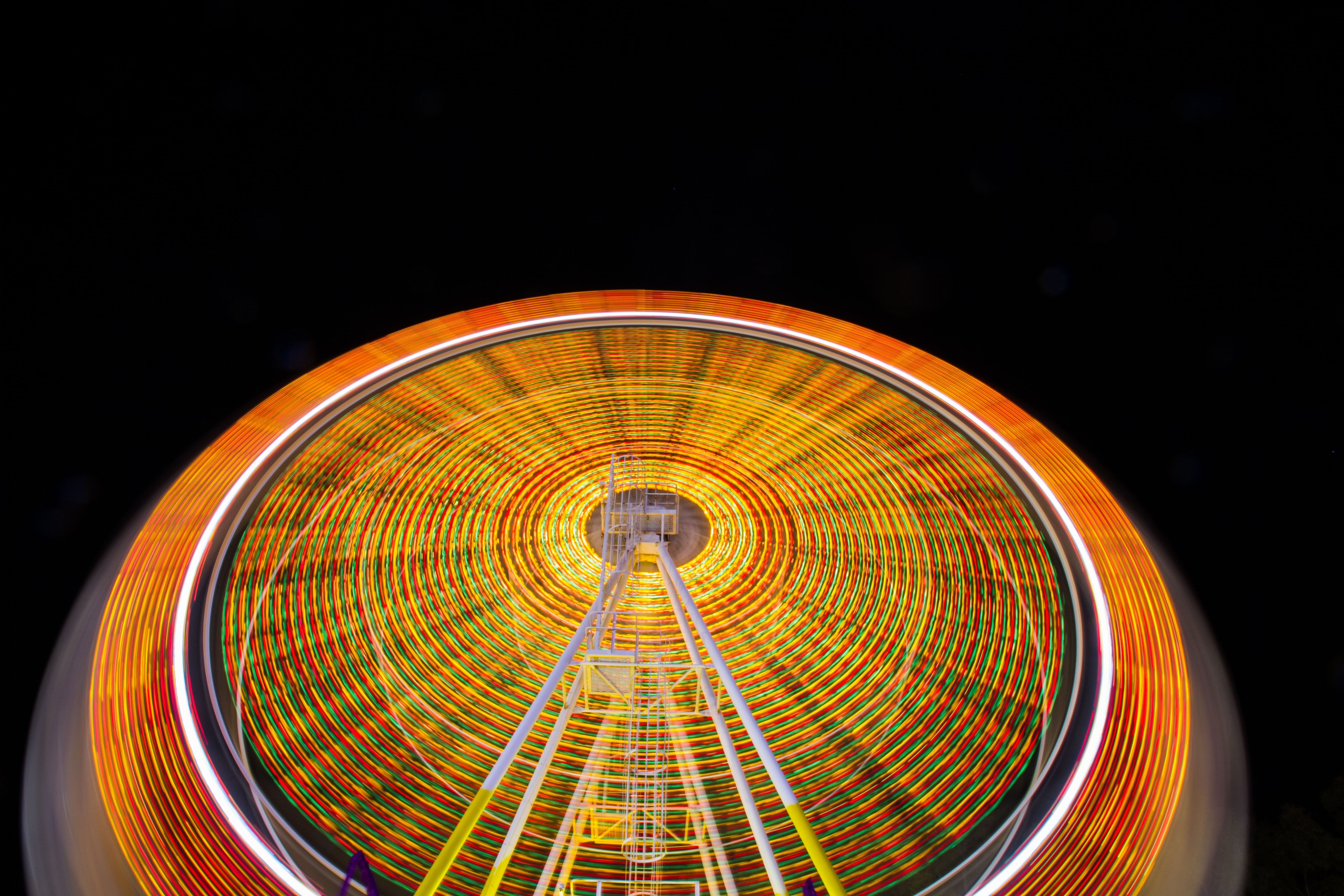 A time exposure shot of a ferris wheel with vivid orange and yellow light trails