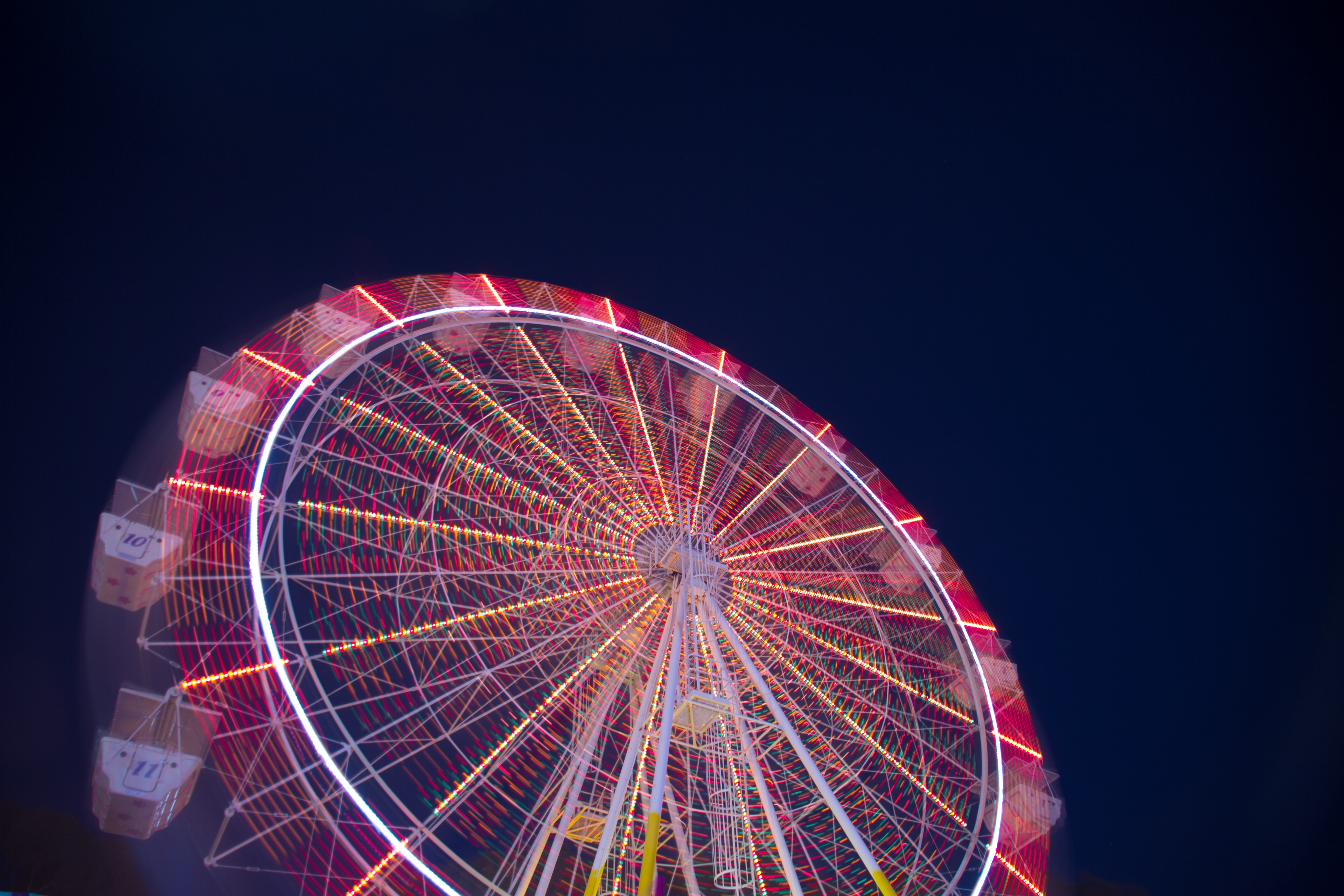 timelapse low angle of white and red ferris wheel