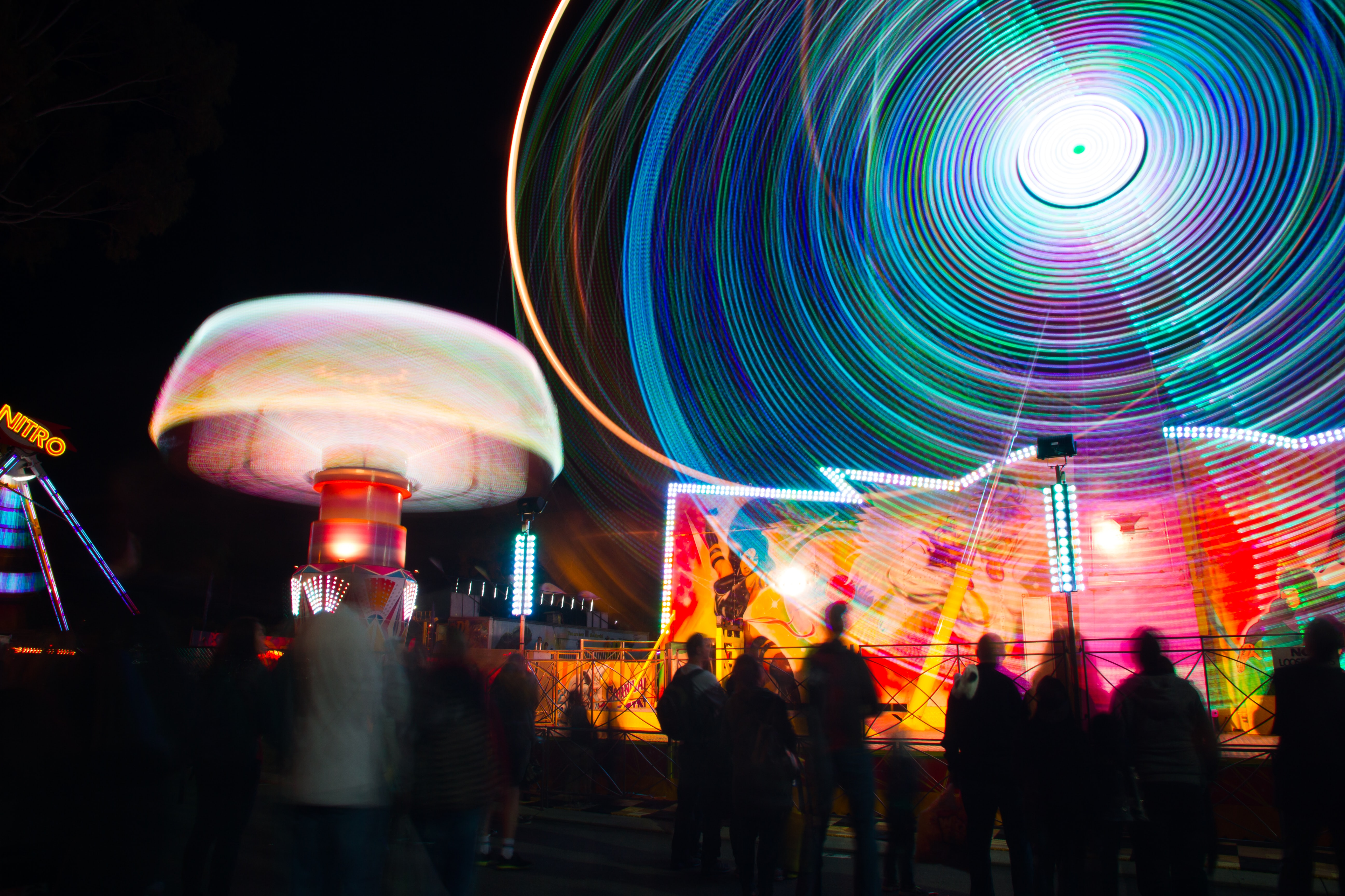 A ride at an amusement park with light trails, plus the Perth Royal Show crowd