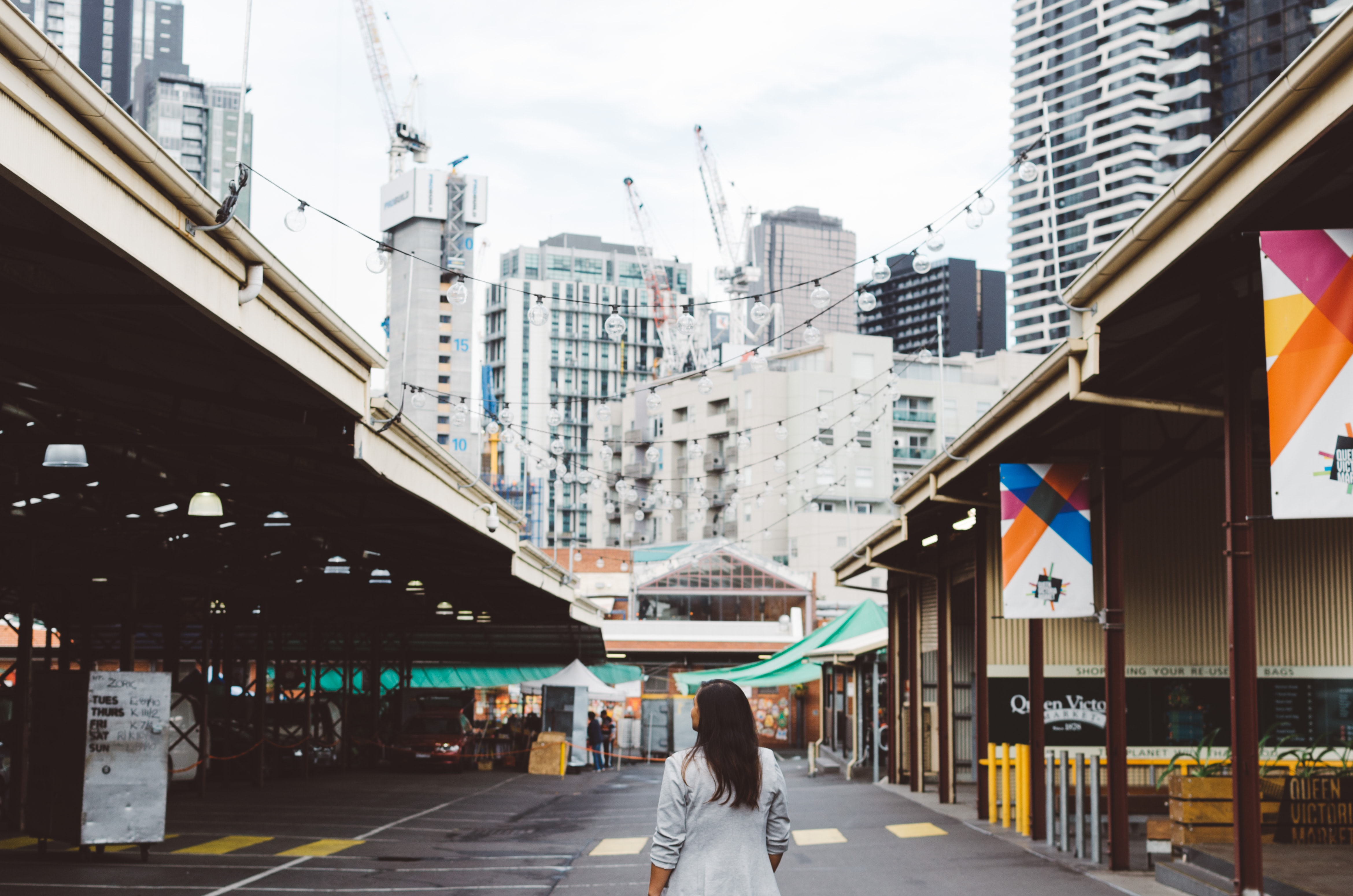 photo of woman standing on roadway between buildings