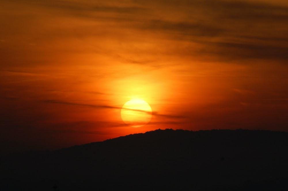 silhouette of mountain during orange sunset