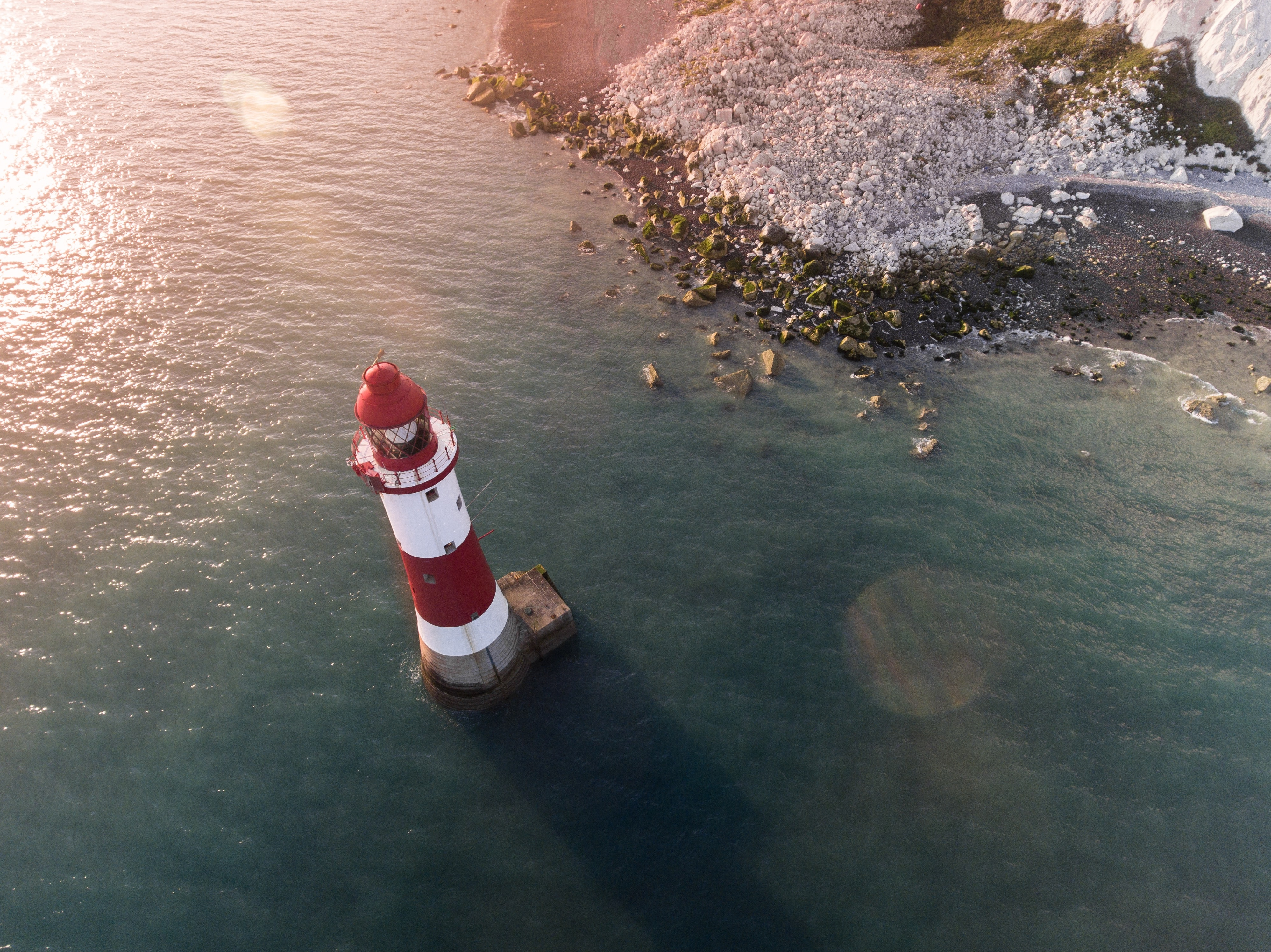 Drone view of the red and white lighthouse by the rocky shoreline at Eastbourne
