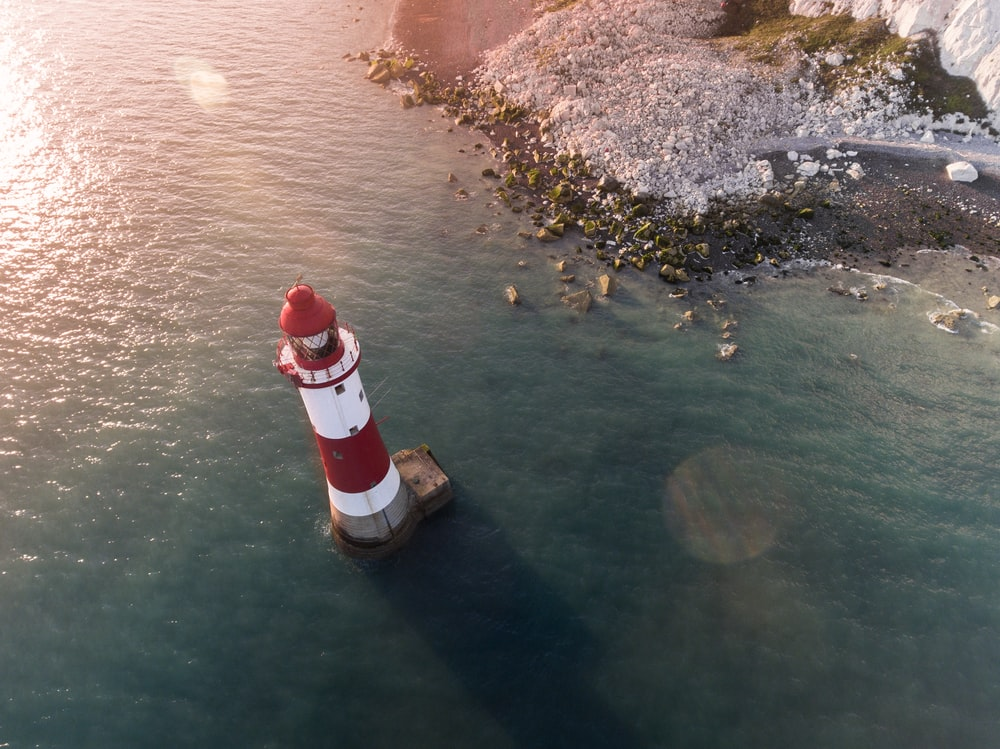 white and red lighthouse in body of water near shore