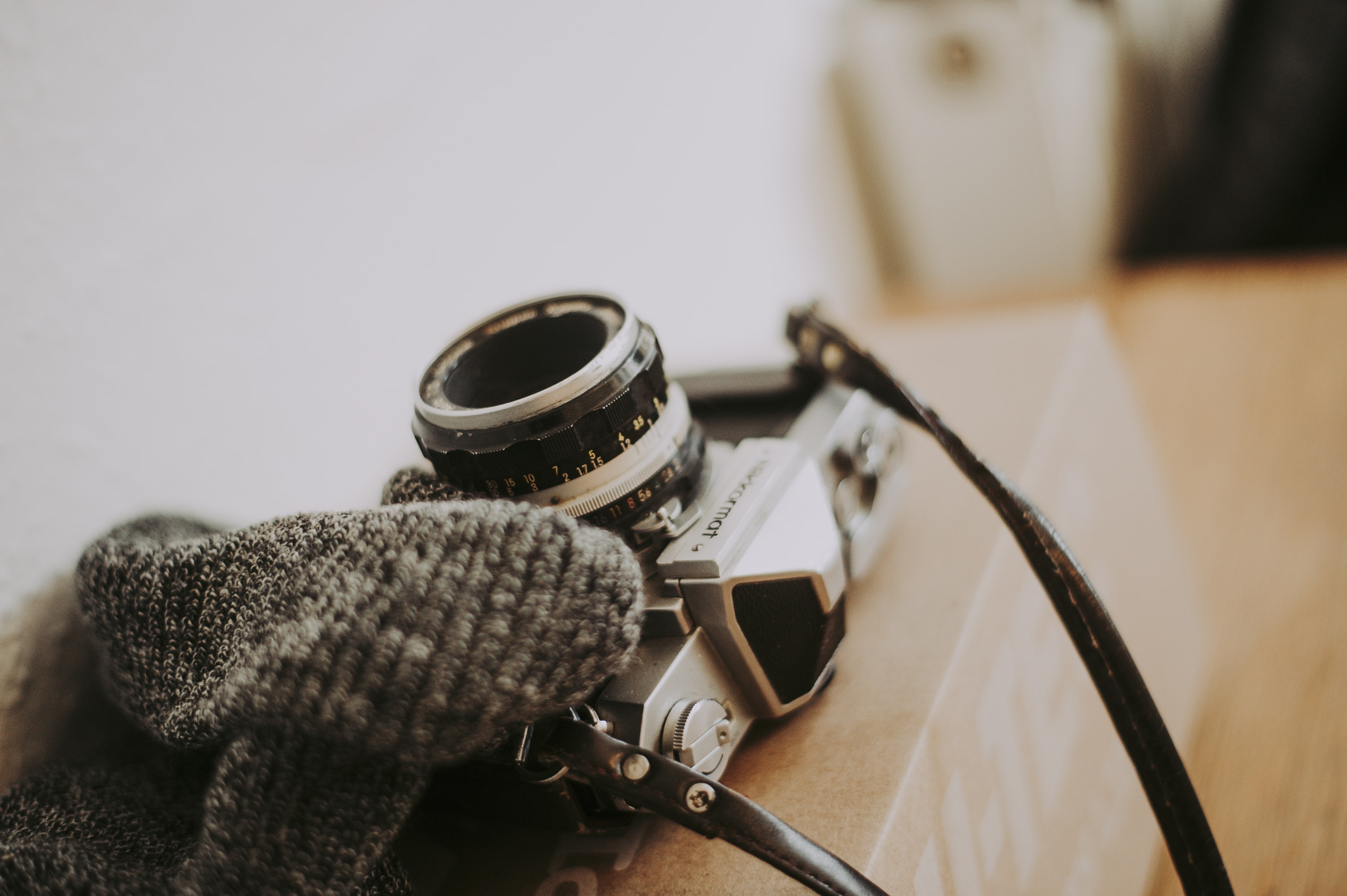 A knit scarf and a vintage camera on a cardboard box