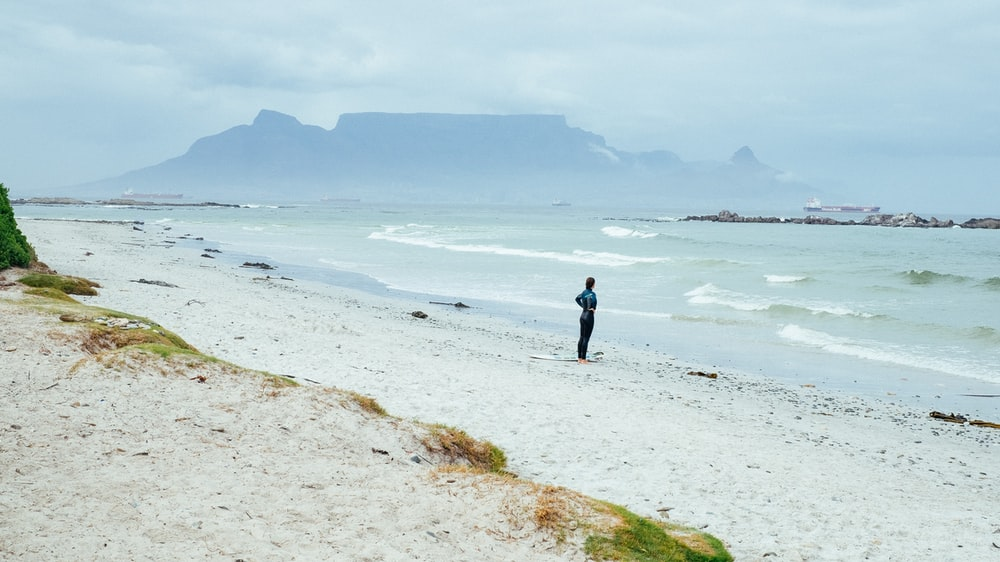 person standing on shore near mountain covering of fogs at daytime