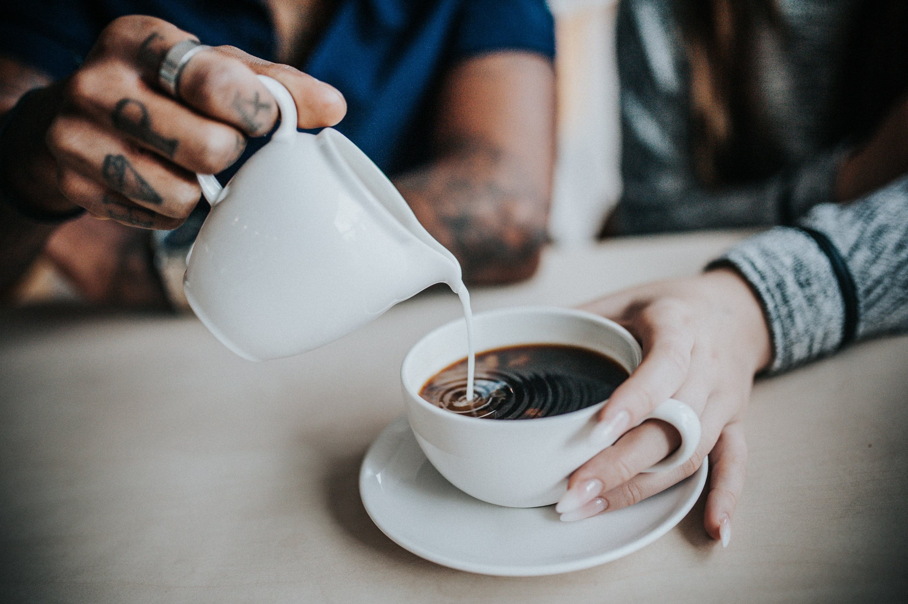 photo of man pouring milk on coffee
