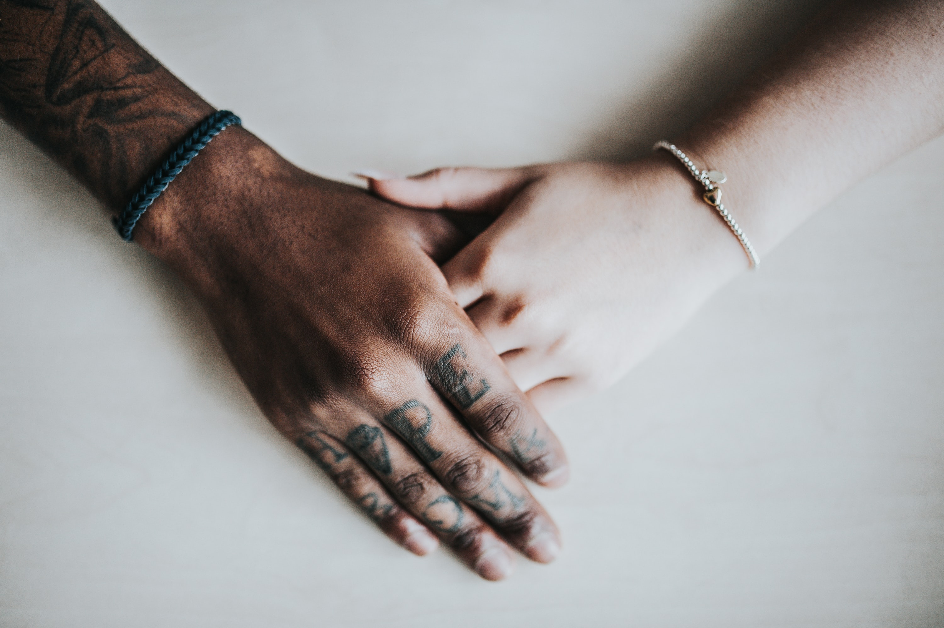 Couple holding hands on a white table