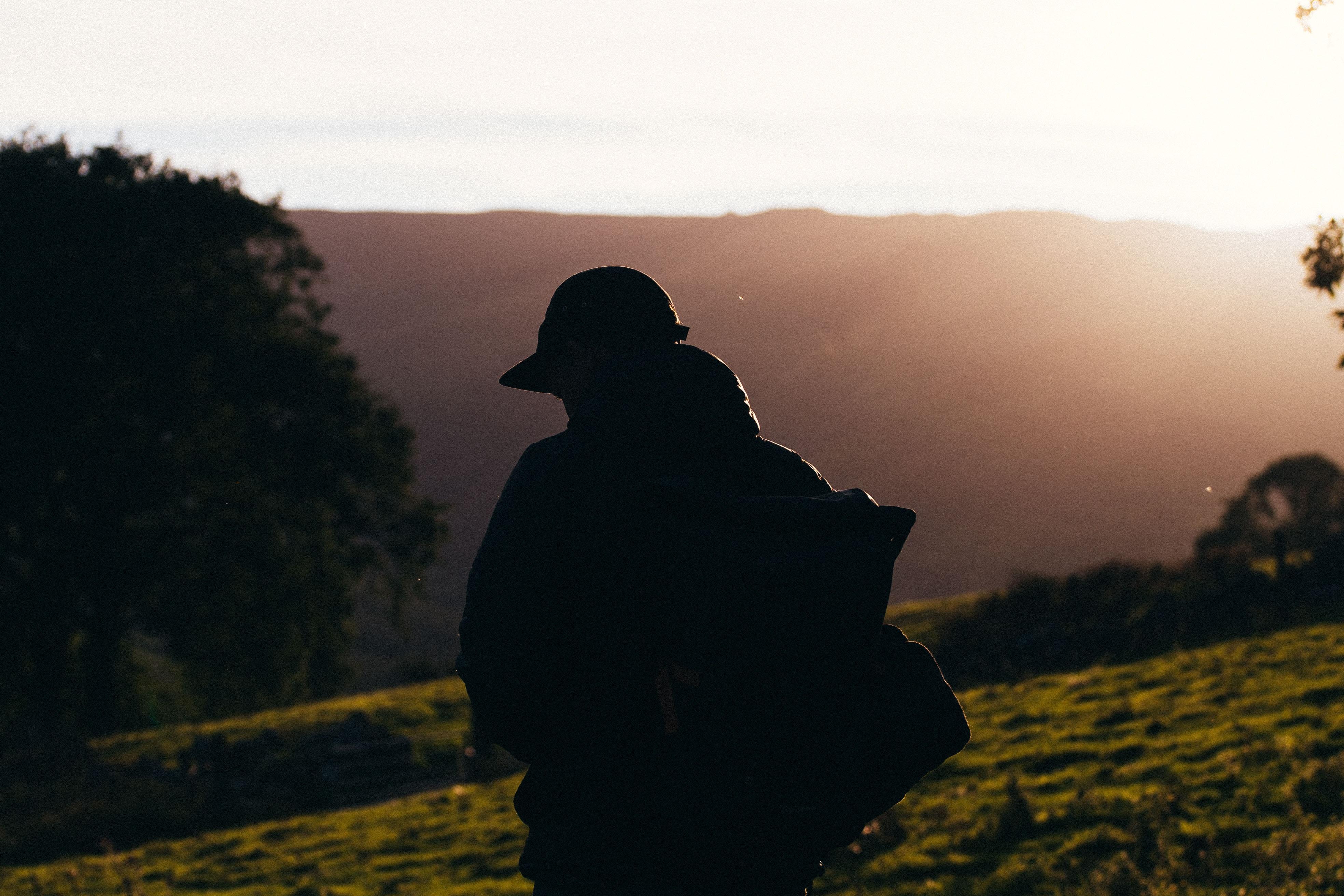 A man hikes through the grass on a mountain in Snowdon