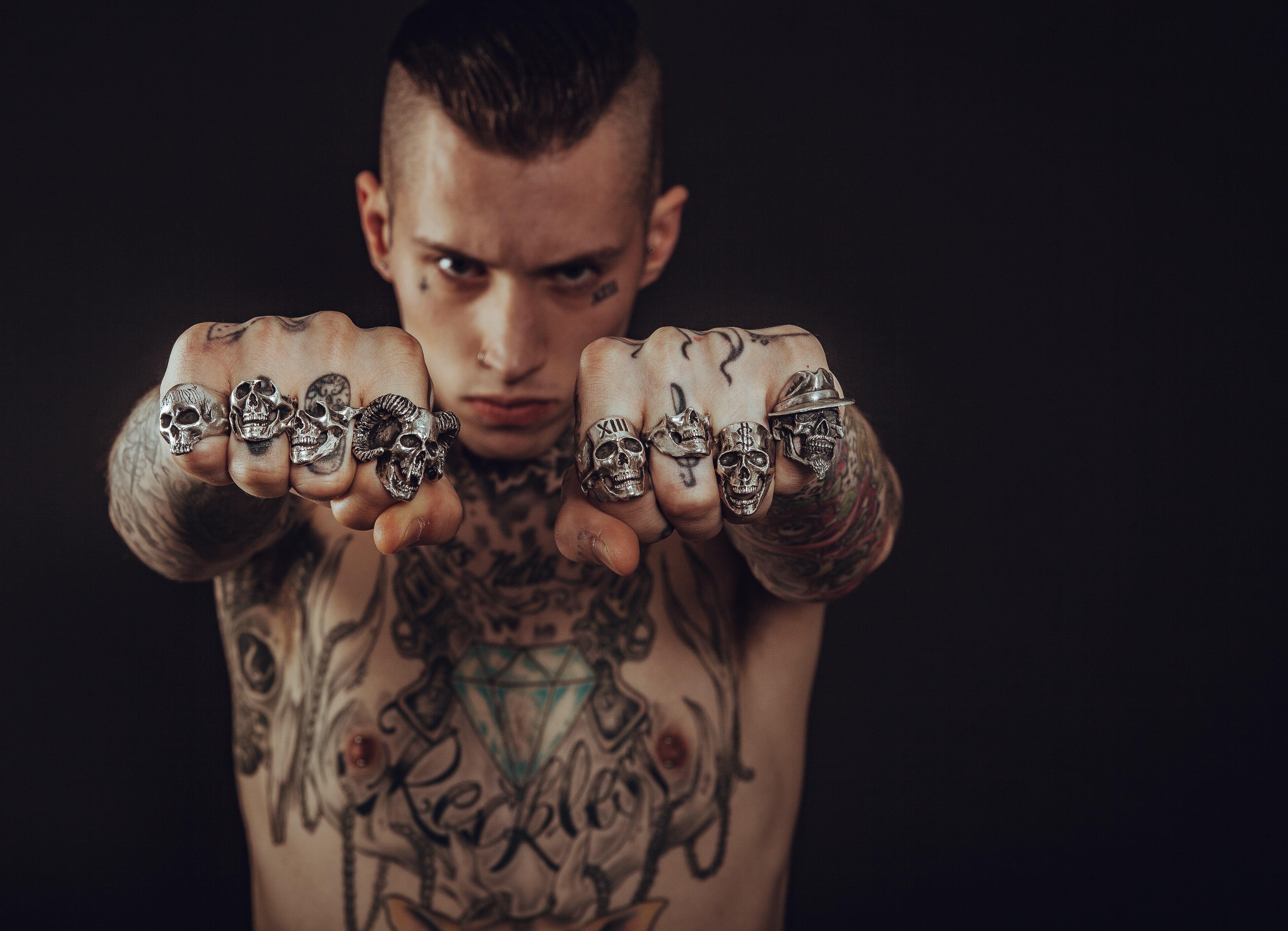 A shirtless man with tattoos on his body and rings on his fingers having a punk haircut in London