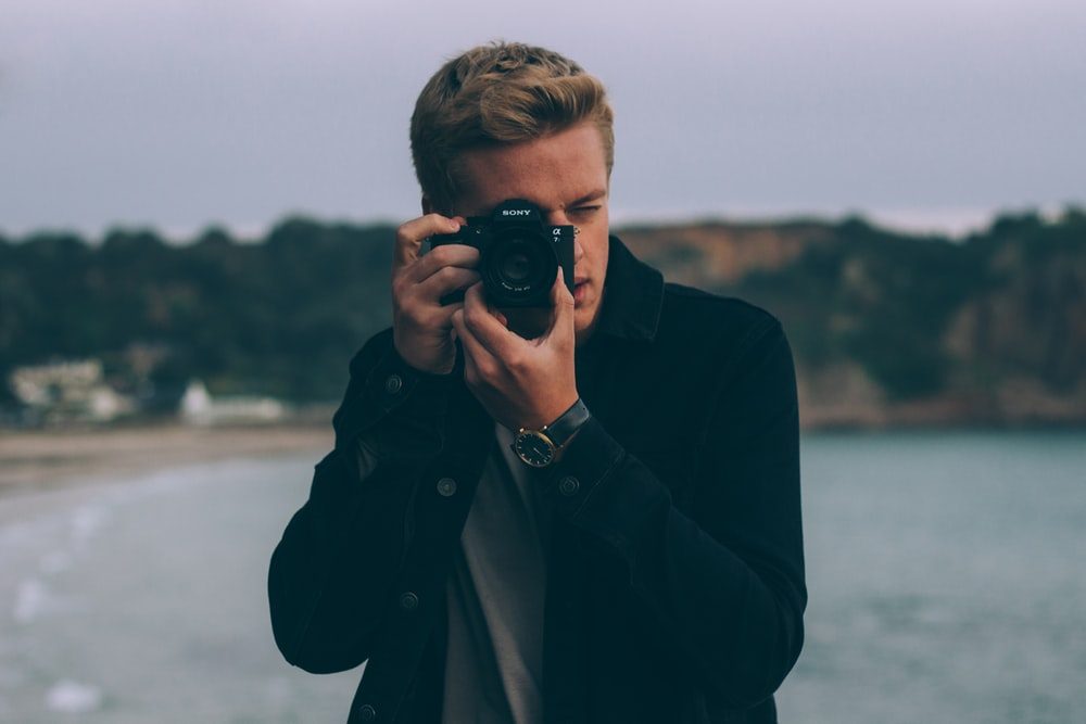 shallow photography of man holding camera