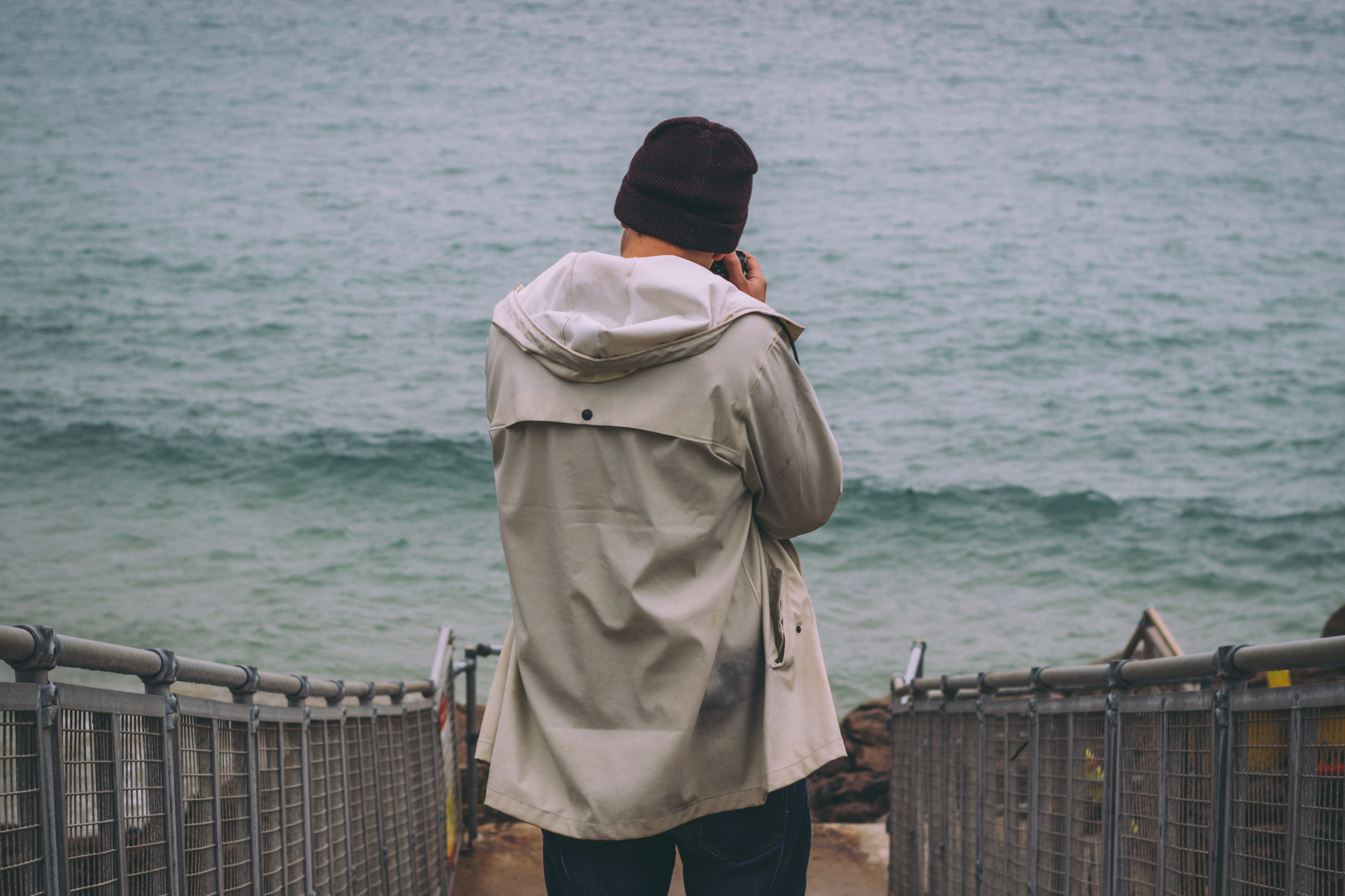 A man wearing a fall jacket on a fenced path, walking toward the sea with a camera
