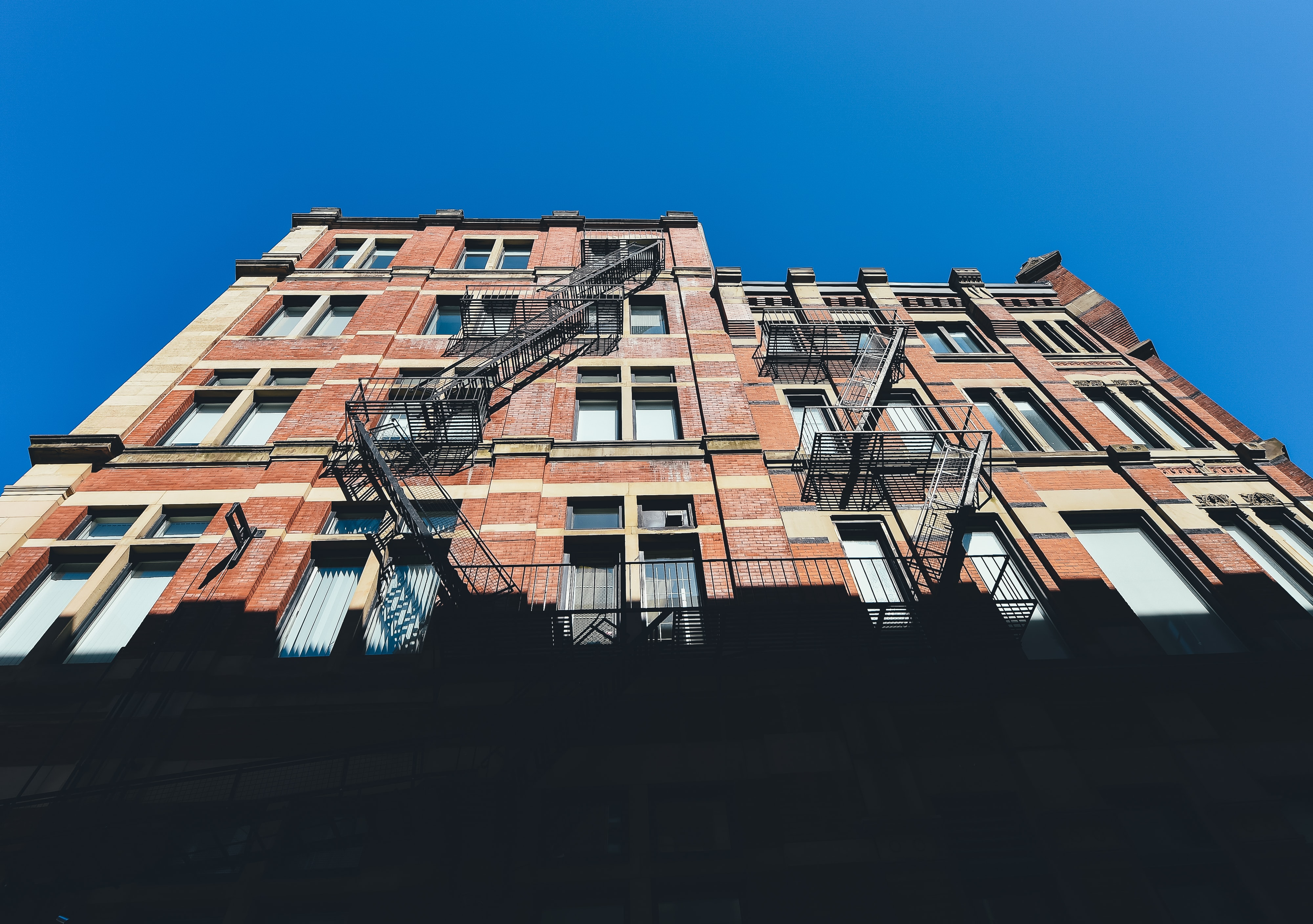 A brick residential building with fire escapes against a blue sky in Montreal