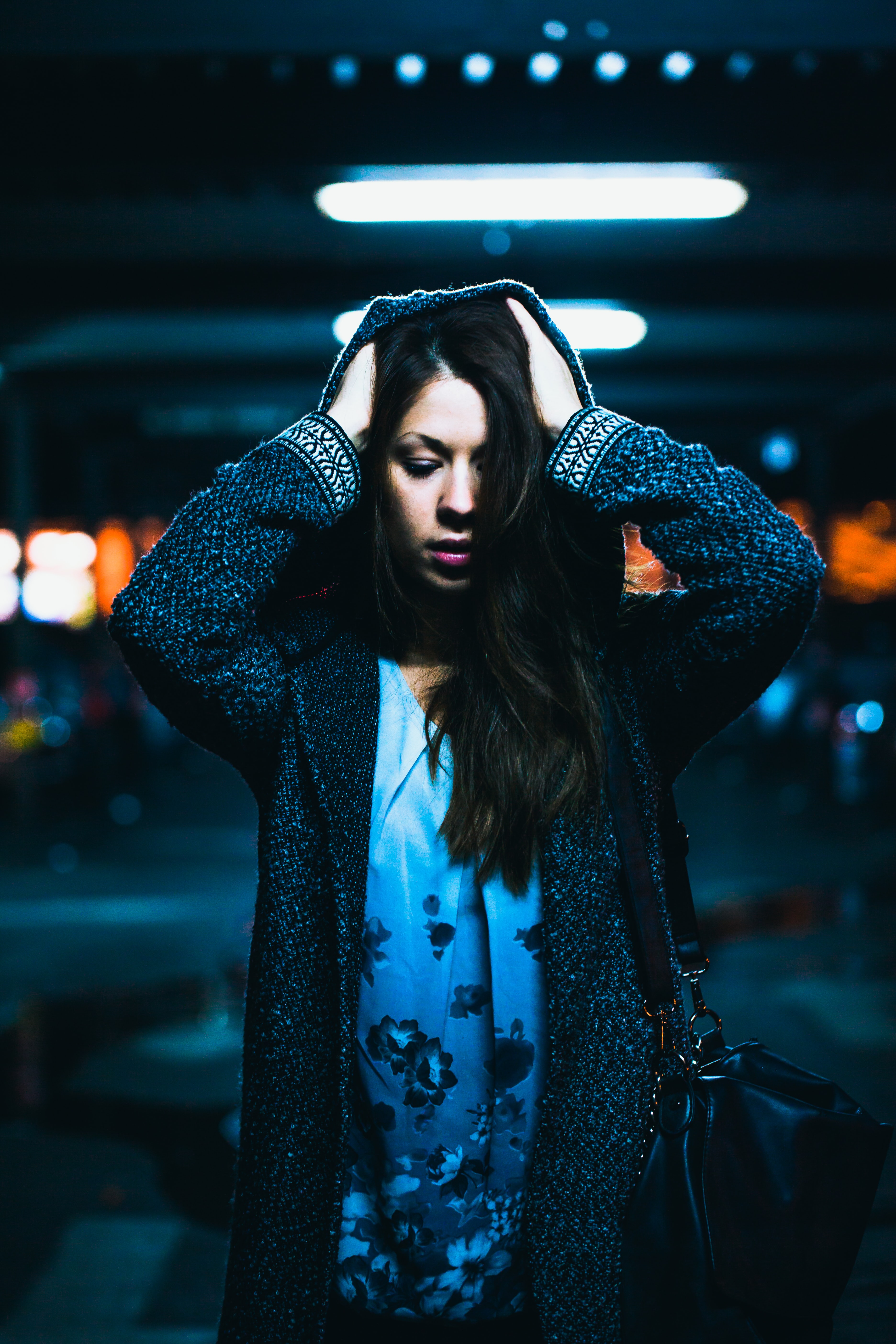 woman wearing hooded cardigan under fluorescent lamp