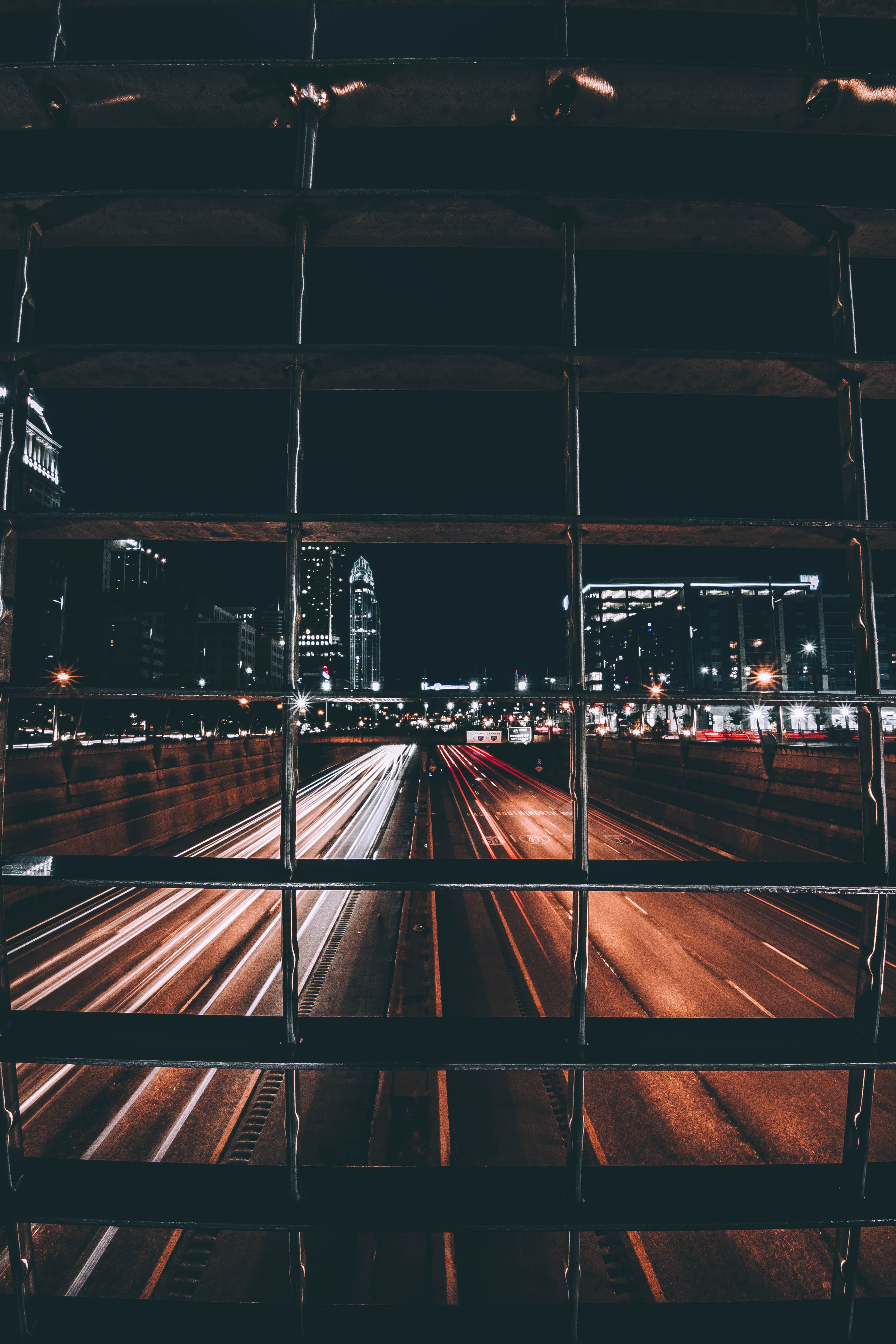 time-lapse photo of road with light streaks view behind grills