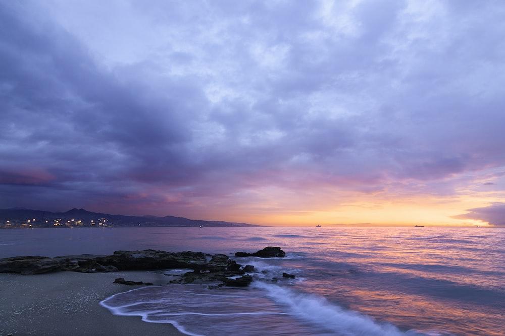 waves of body of water splashing on sand