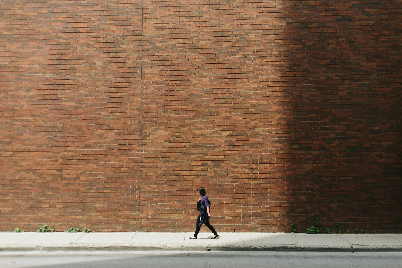woman in black shirt walking on sidewalk near brown concrete wall partition