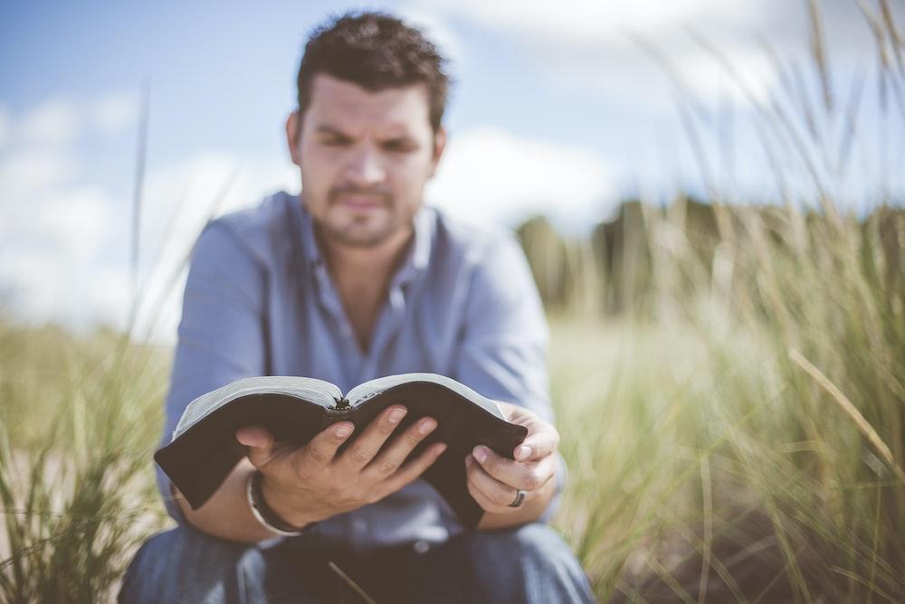 man reading book in grass field