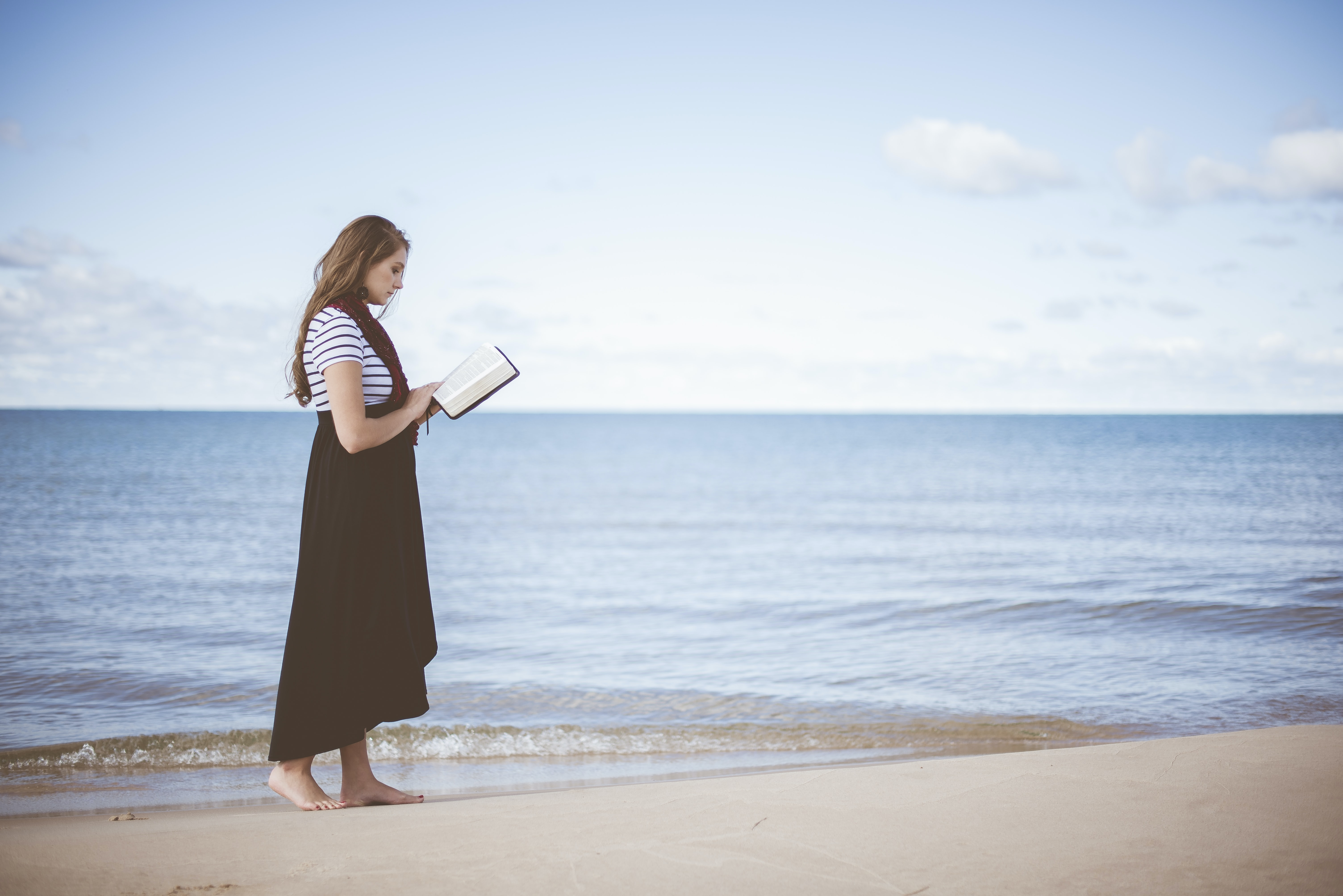 A woman standing in the sand while reading a book on a beach.