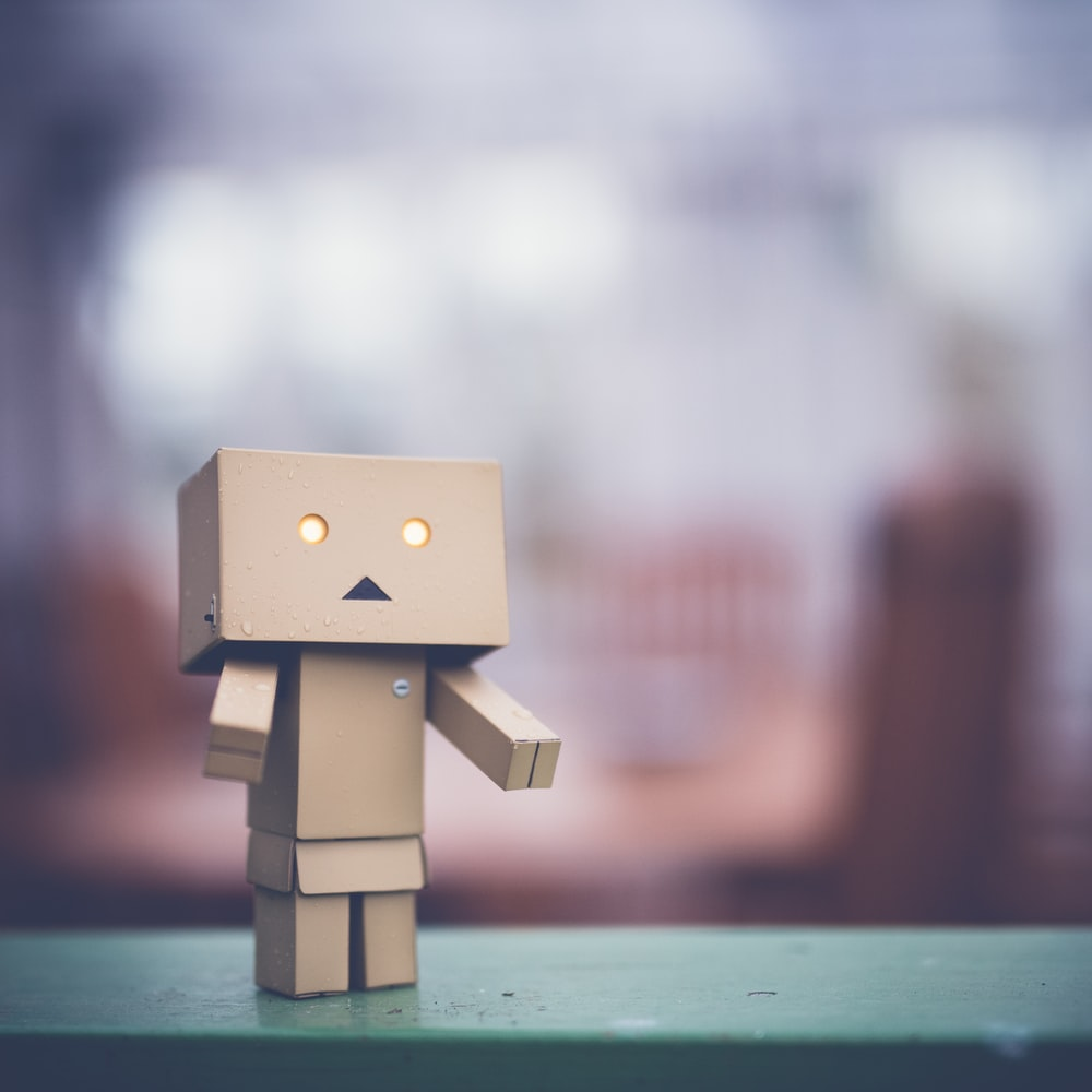 brown cardboard robot on green table