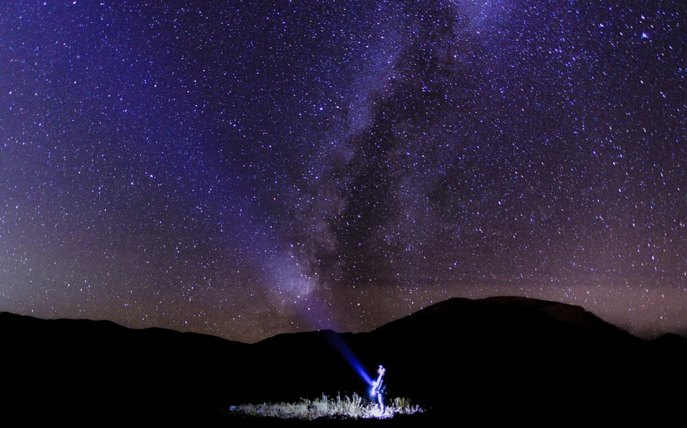 person holding light in milky way