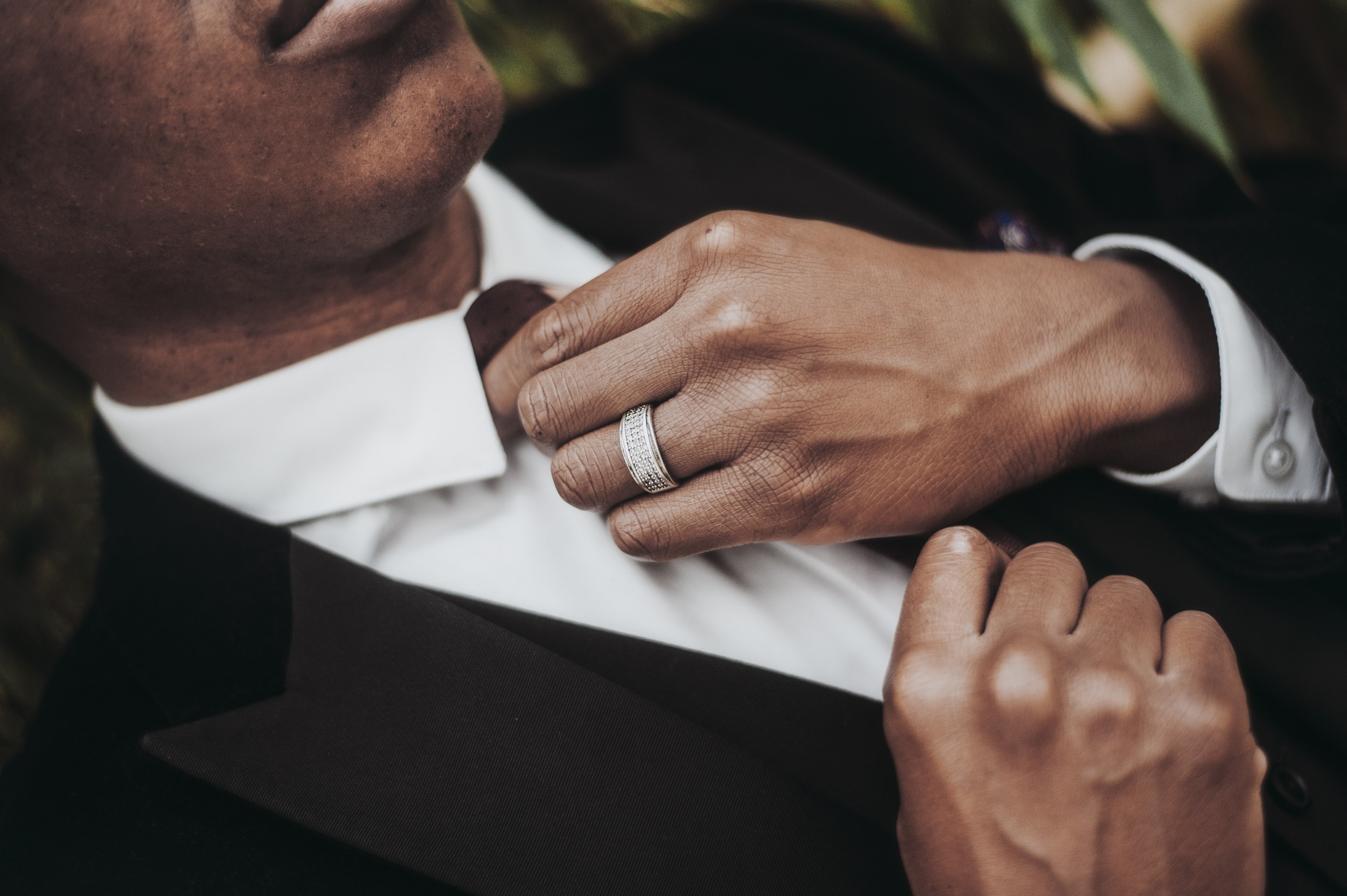 Groom adjusts his tie against white shirt and black suit
