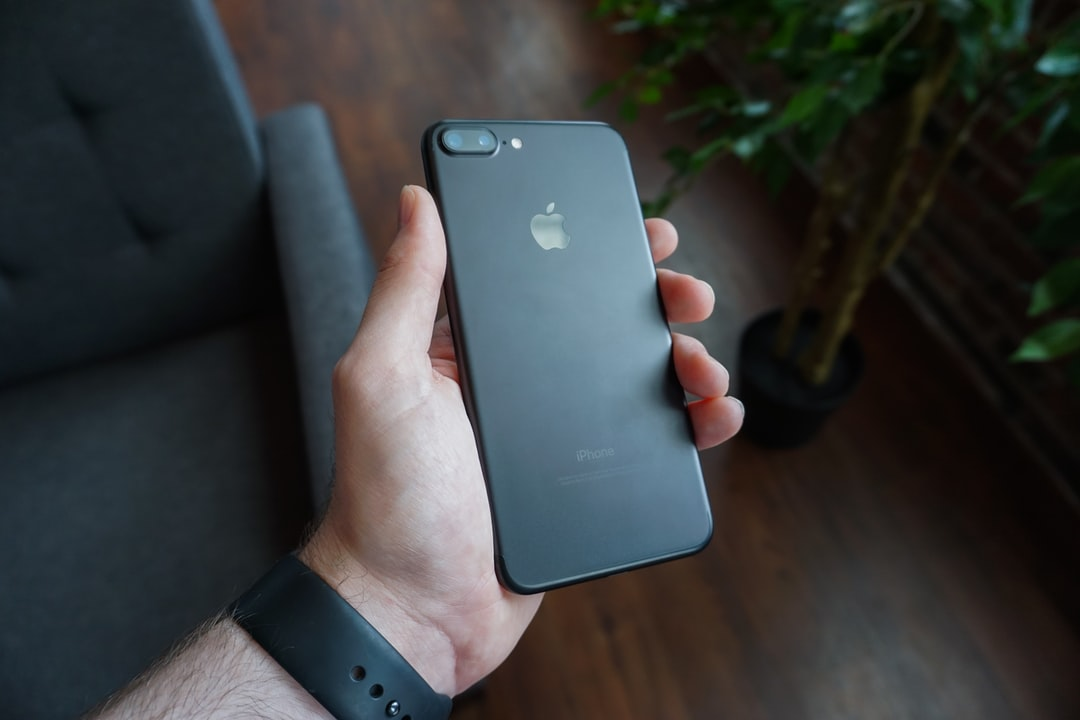 A person's hand holding a black iPhone 7