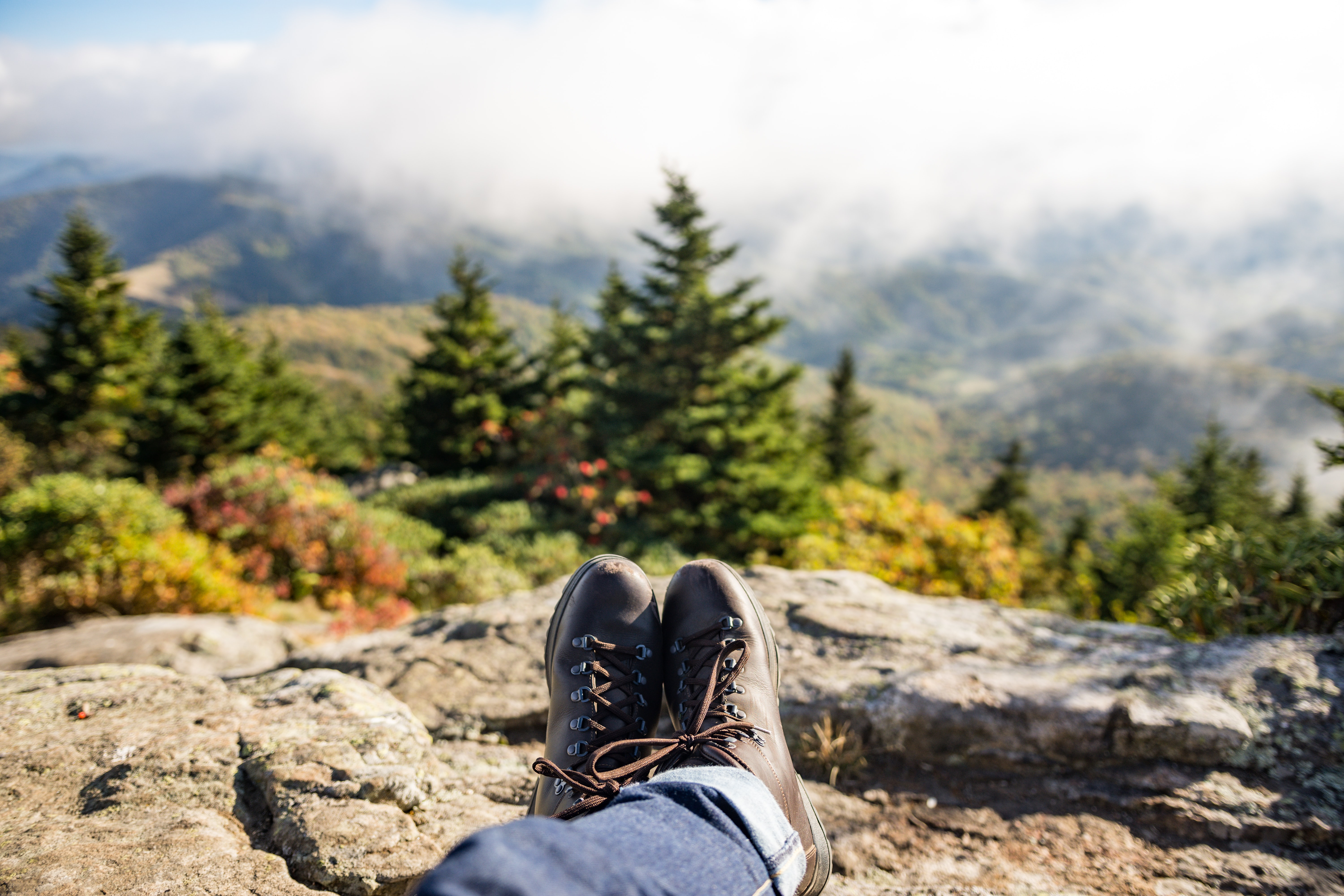 A person wearing hiking boots and jeans resting on a rock looking out into the fog covered mountains