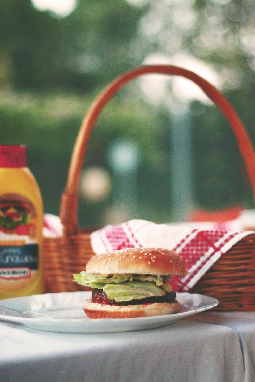 hamburger on ceramic plate beside picnic basket